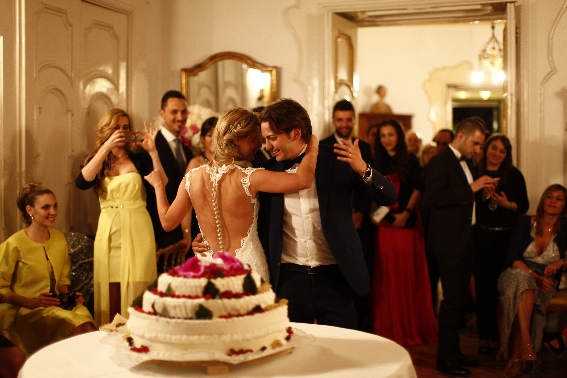 pasquale andreotti bride and groom dancing beyond the wedding cake