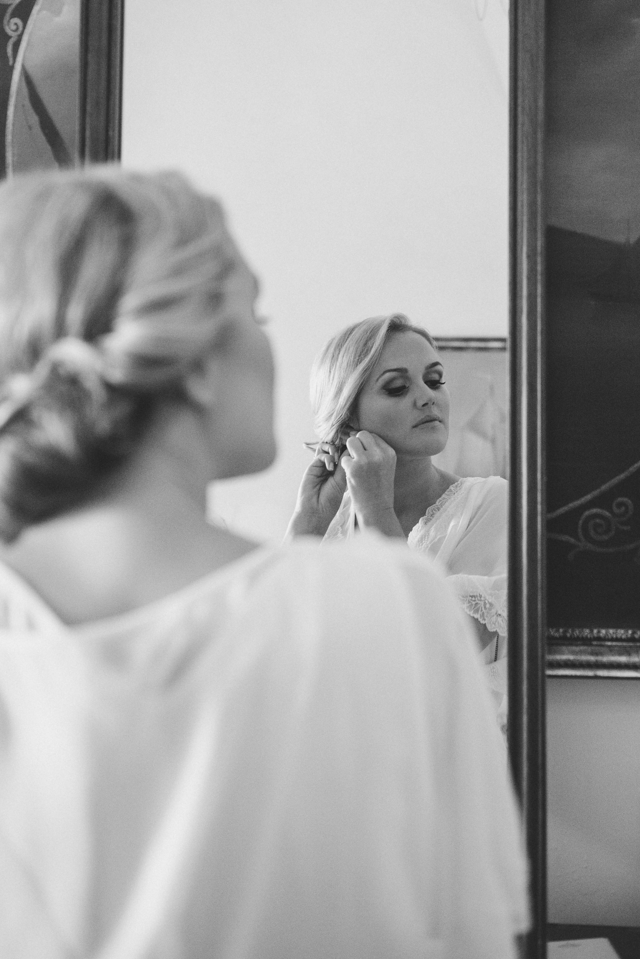 the bride wears her earrings