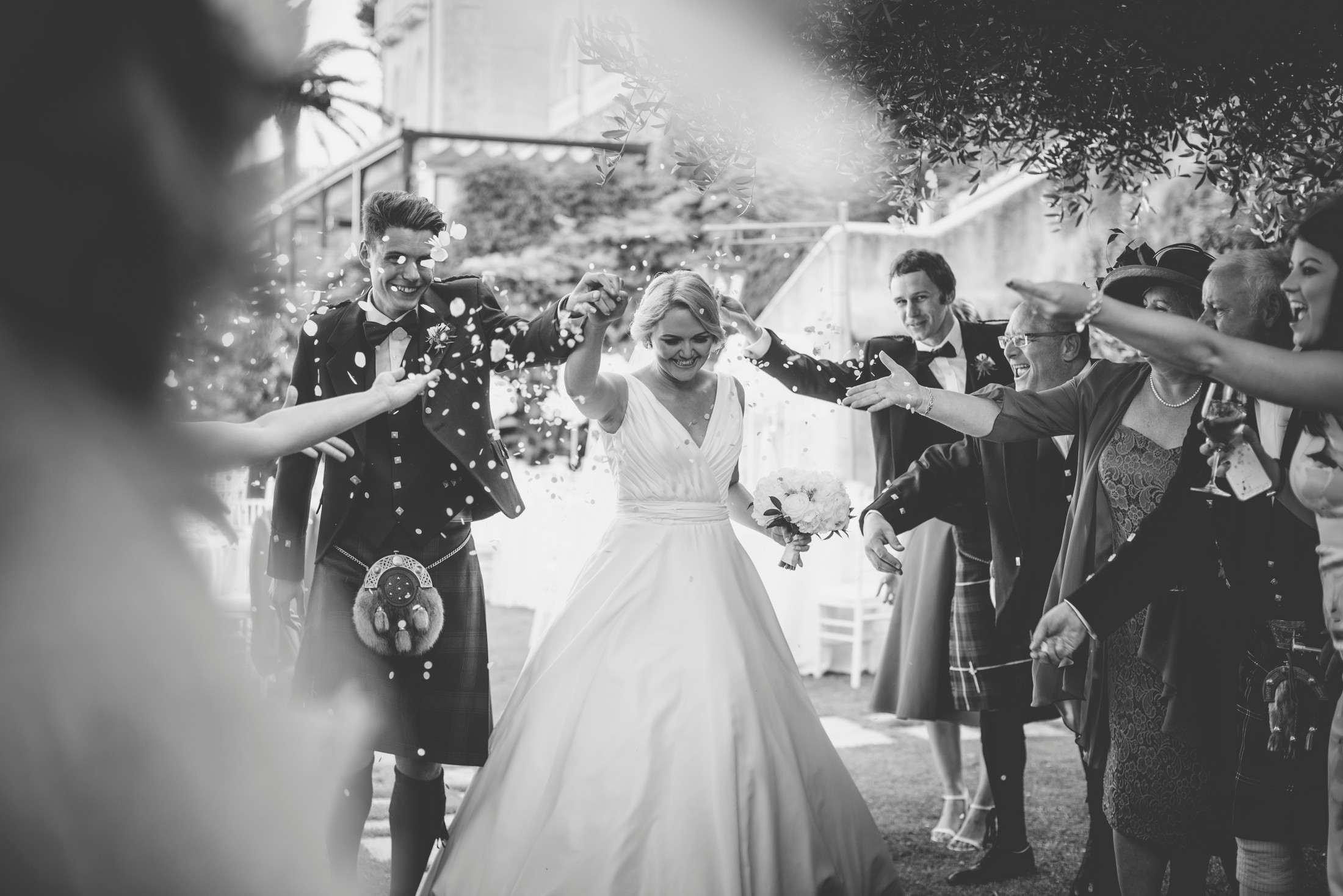 wedding guests throwing petals to the bride and the groom