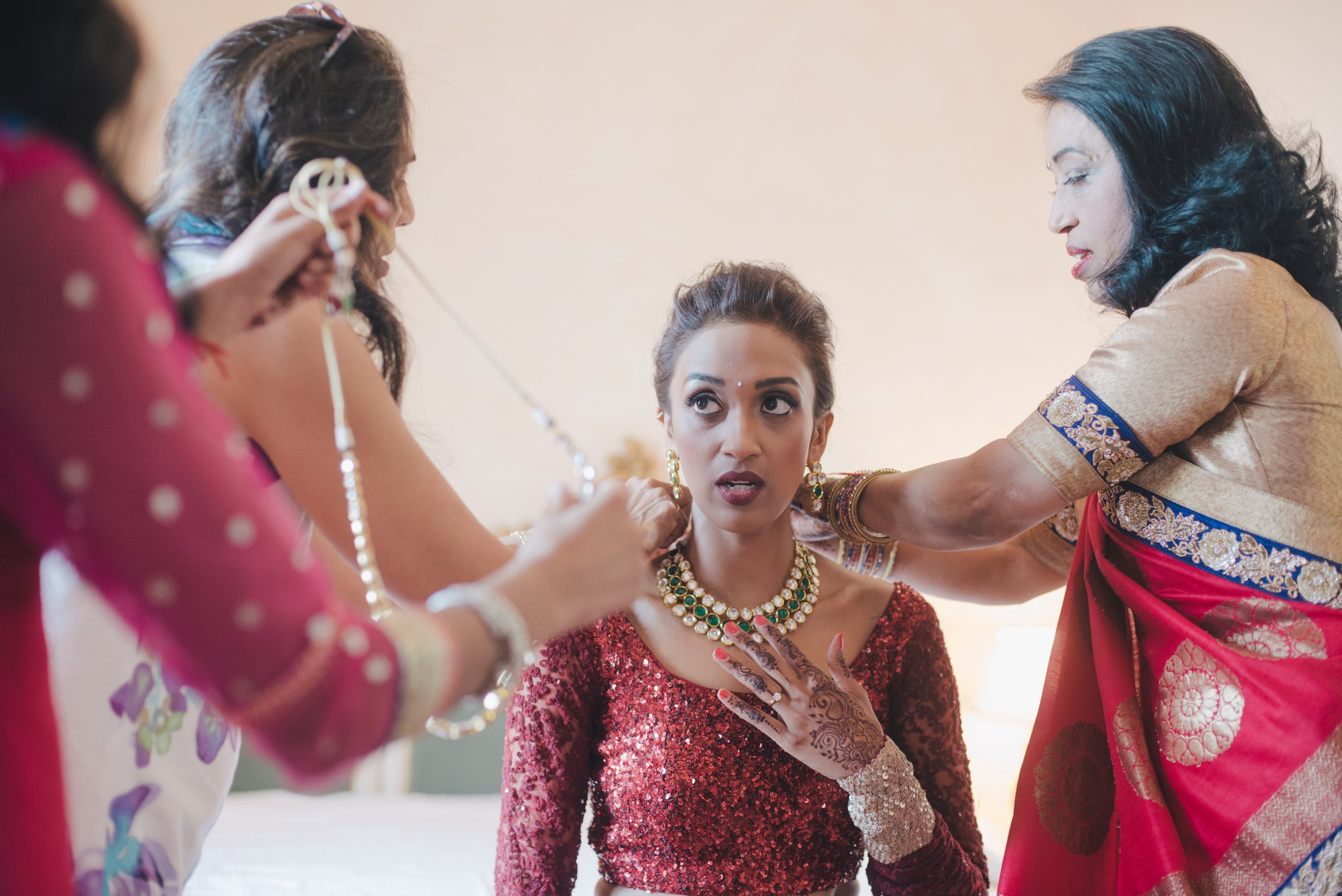 indian bride getting dressed with her mather and friends