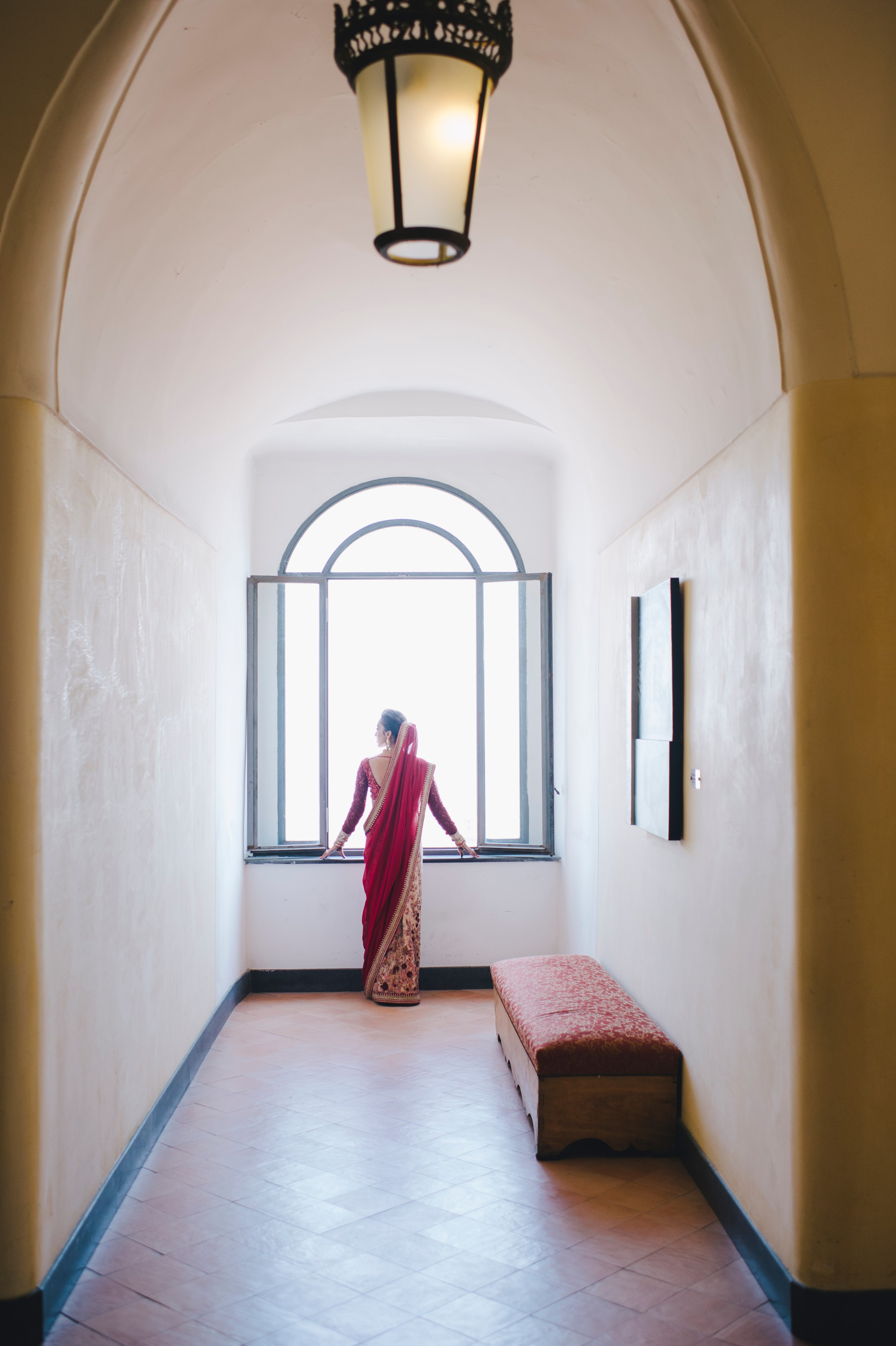 bride's portrait by a big window with red indian typical wedding dress