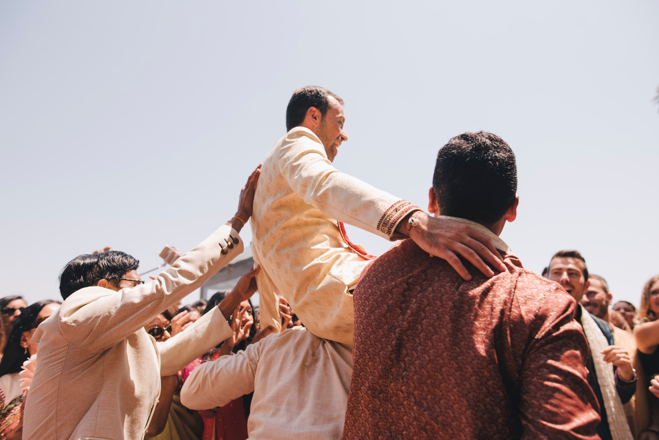 indian wedding guests bring the groom around on their shoulders