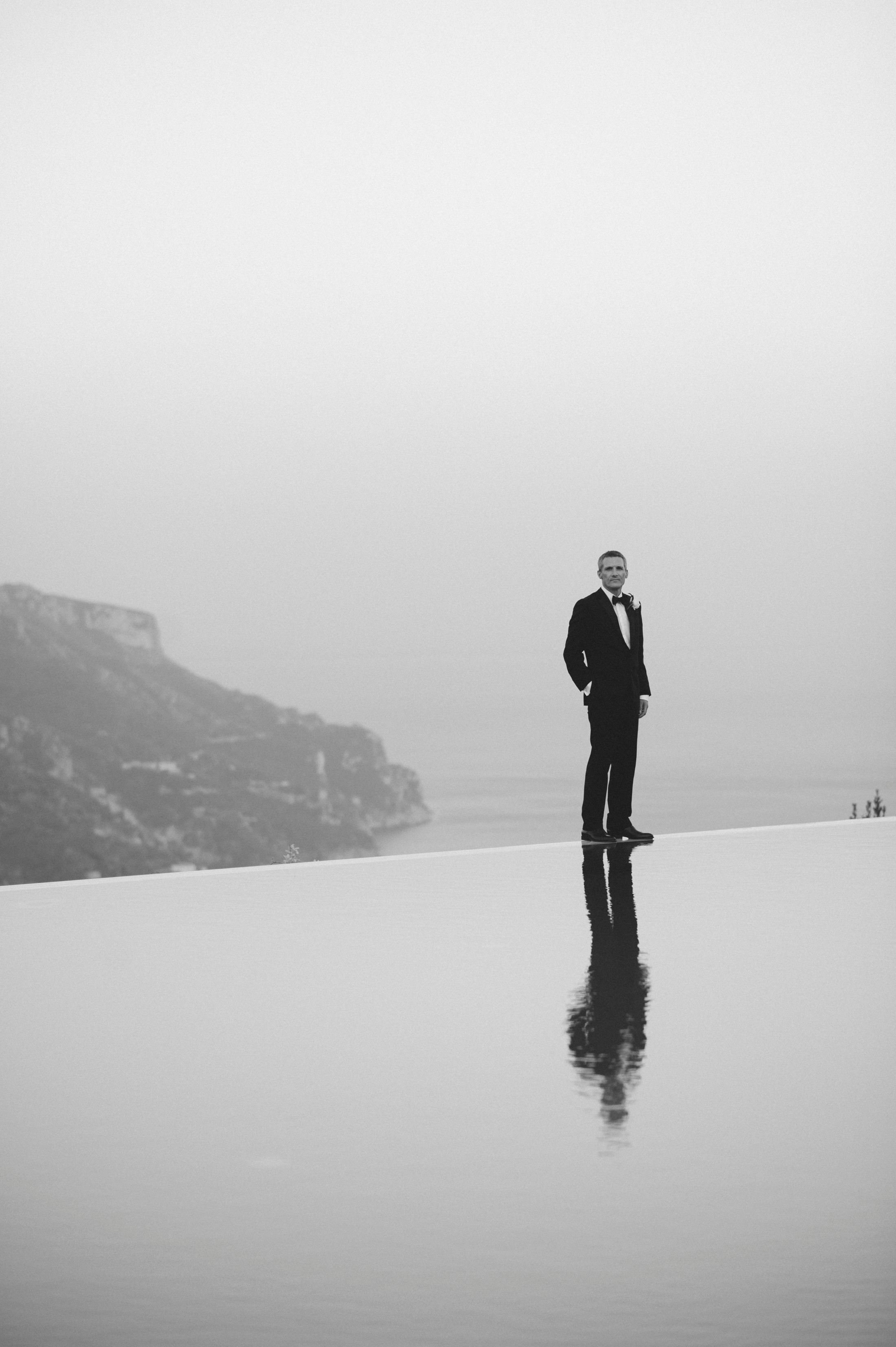 wedding in ravello groom's portrait by the infinity pool in black and white