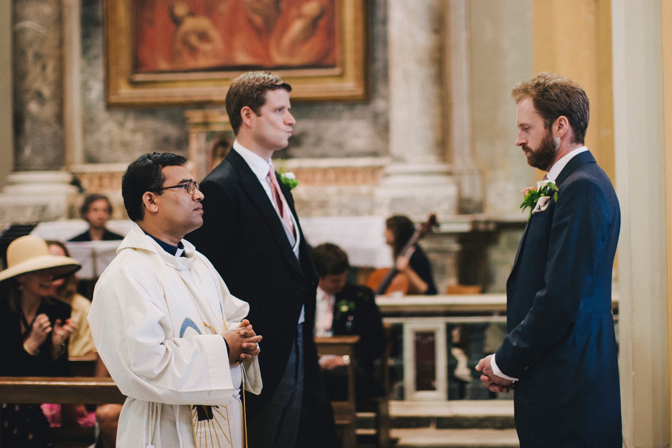 wedding in rome the groom with his best man and the priest inside the church