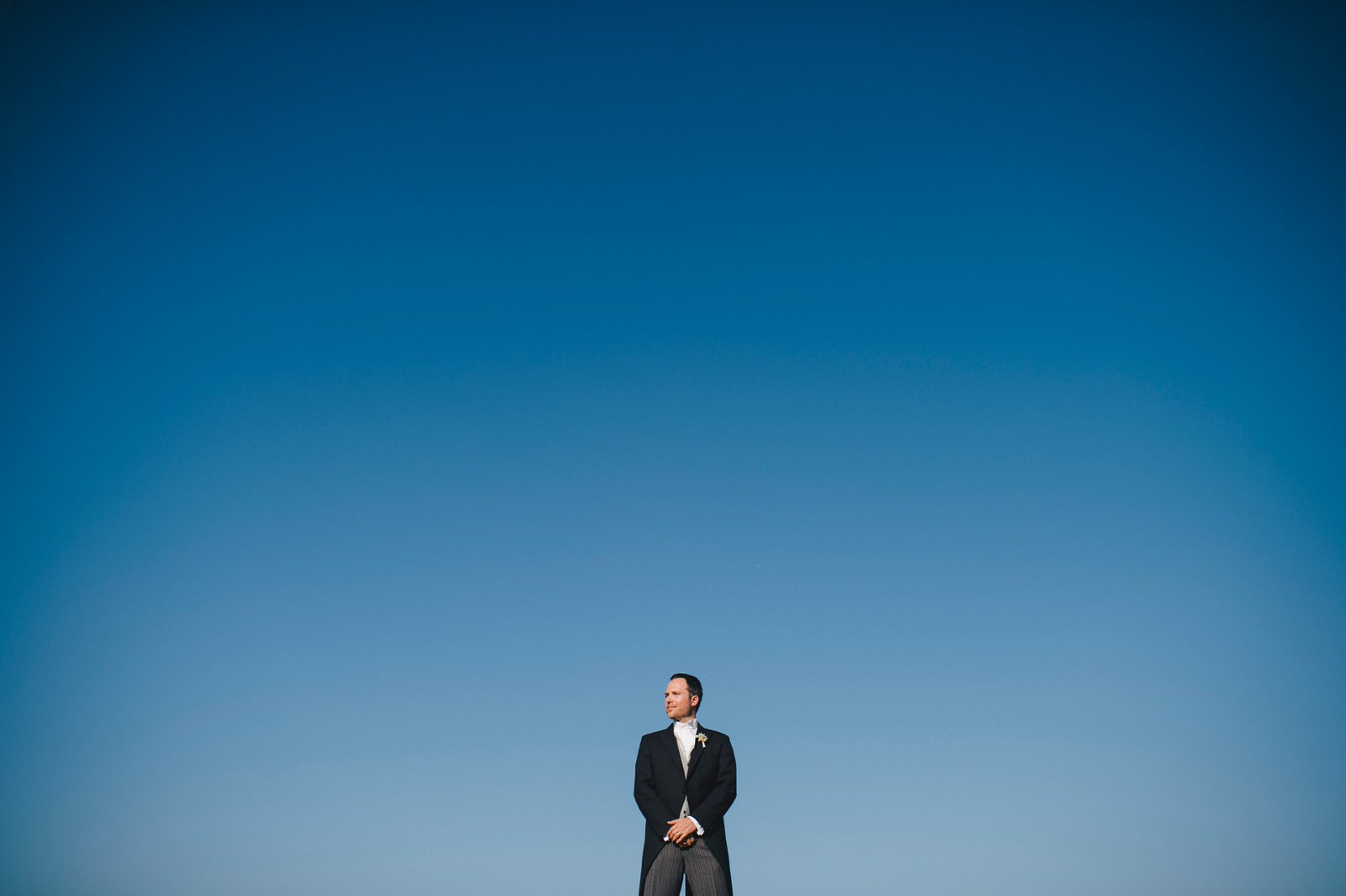 tuscany wedding groom's portrait with the blue sky as backdrop