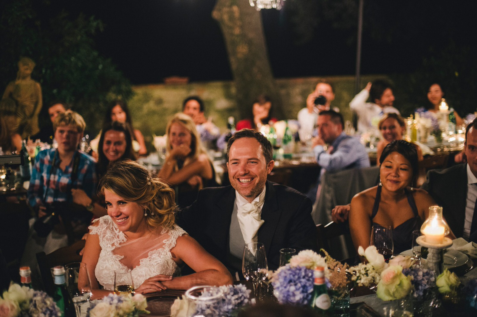 tuscany wedding bride and groom listening to the best man speech and laughing