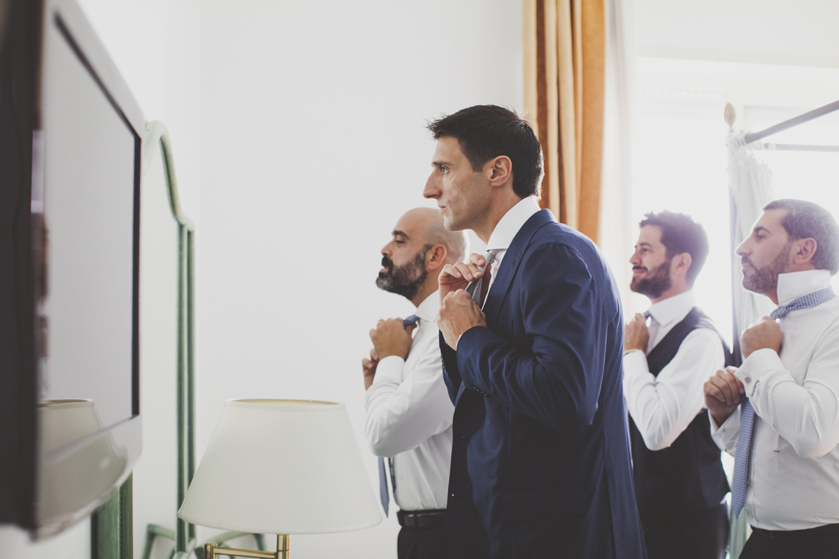 wedding in amalfi the groom with his best men looking at themselves in a mirror and wearing the tie