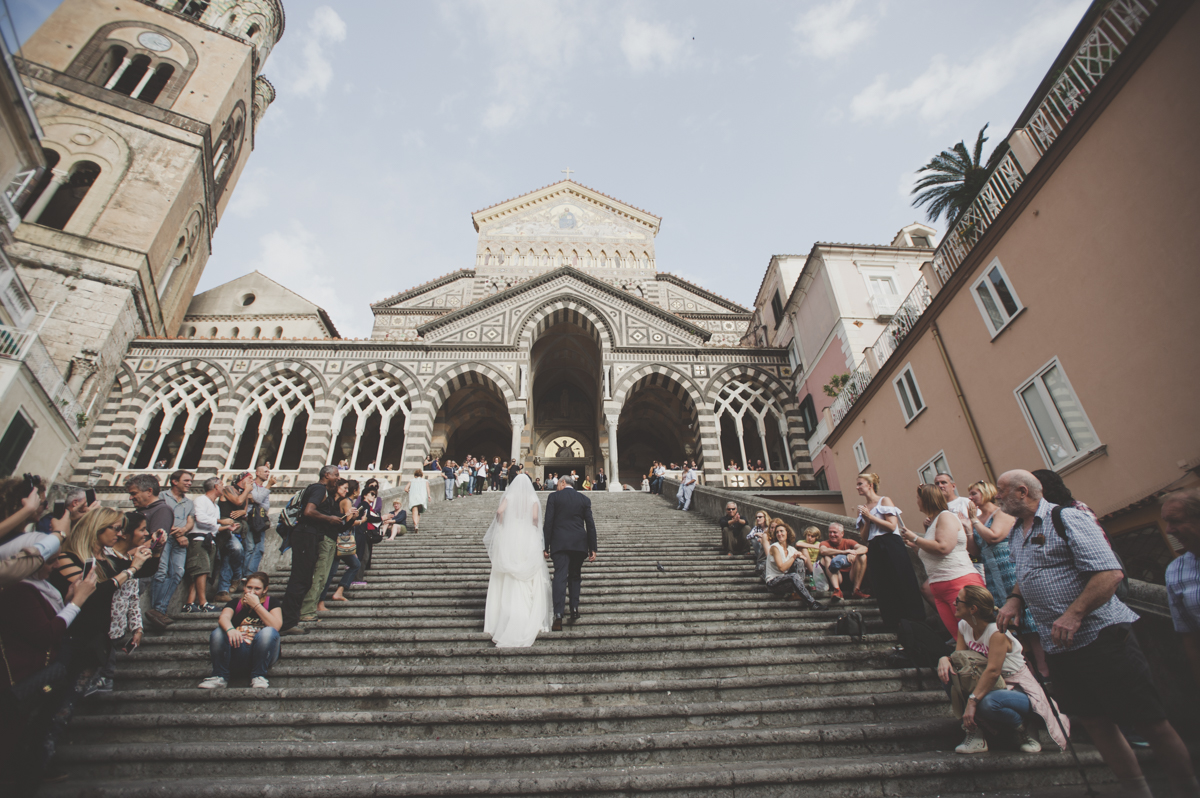 wedding in amalfi the bride with her father going up the stairs to the amalfi cathedral