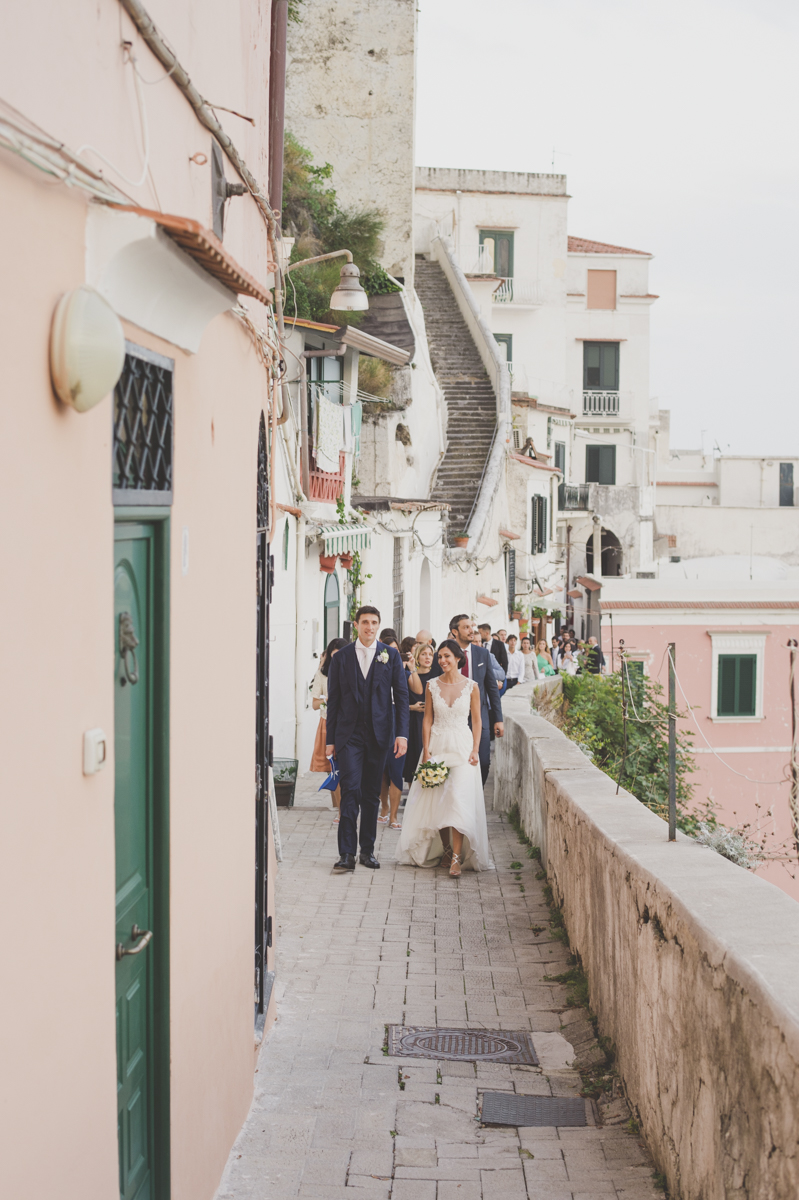 wedding in amalfi the bride and the groom walking together followed by their guests