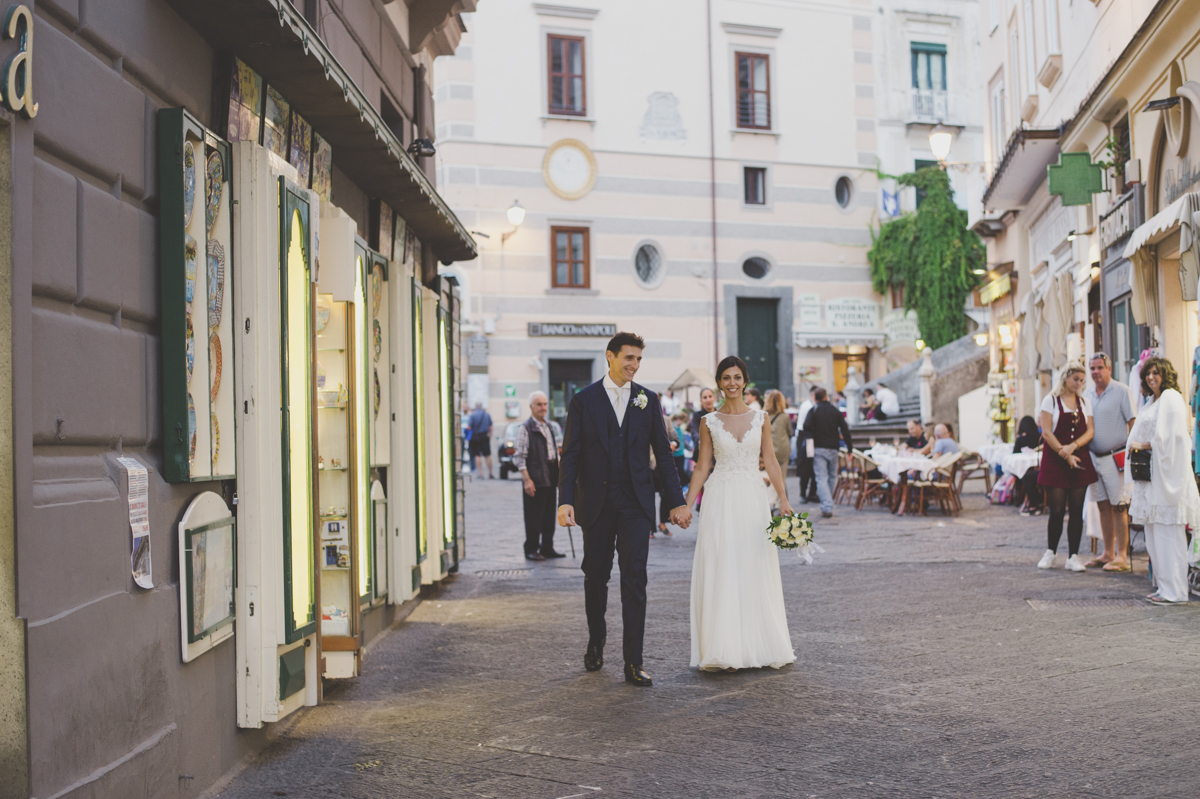 wedding in amalfi the bride and the groom walking together on the square.