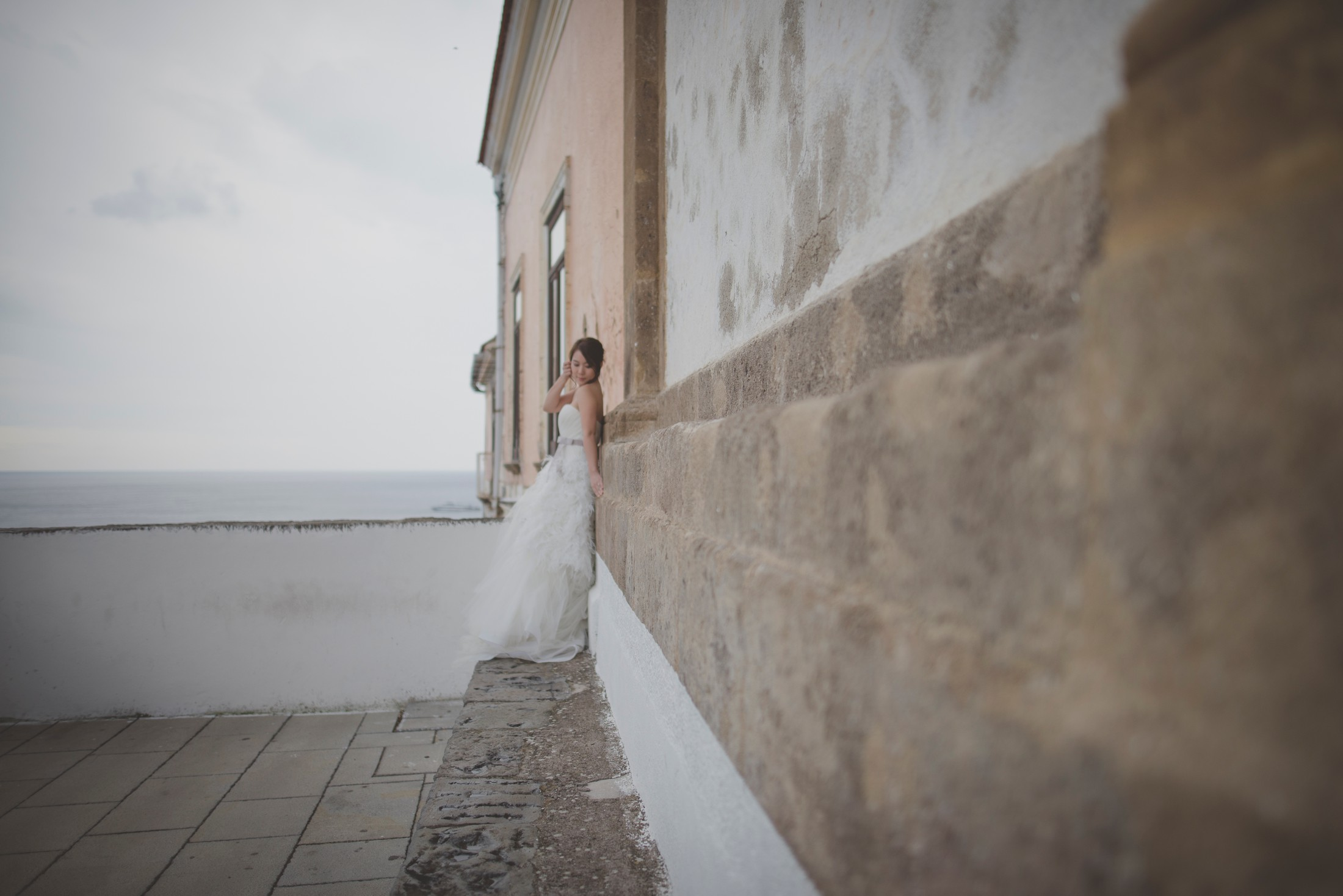 wedding on the amalfi coast the brides leans against a pink wall