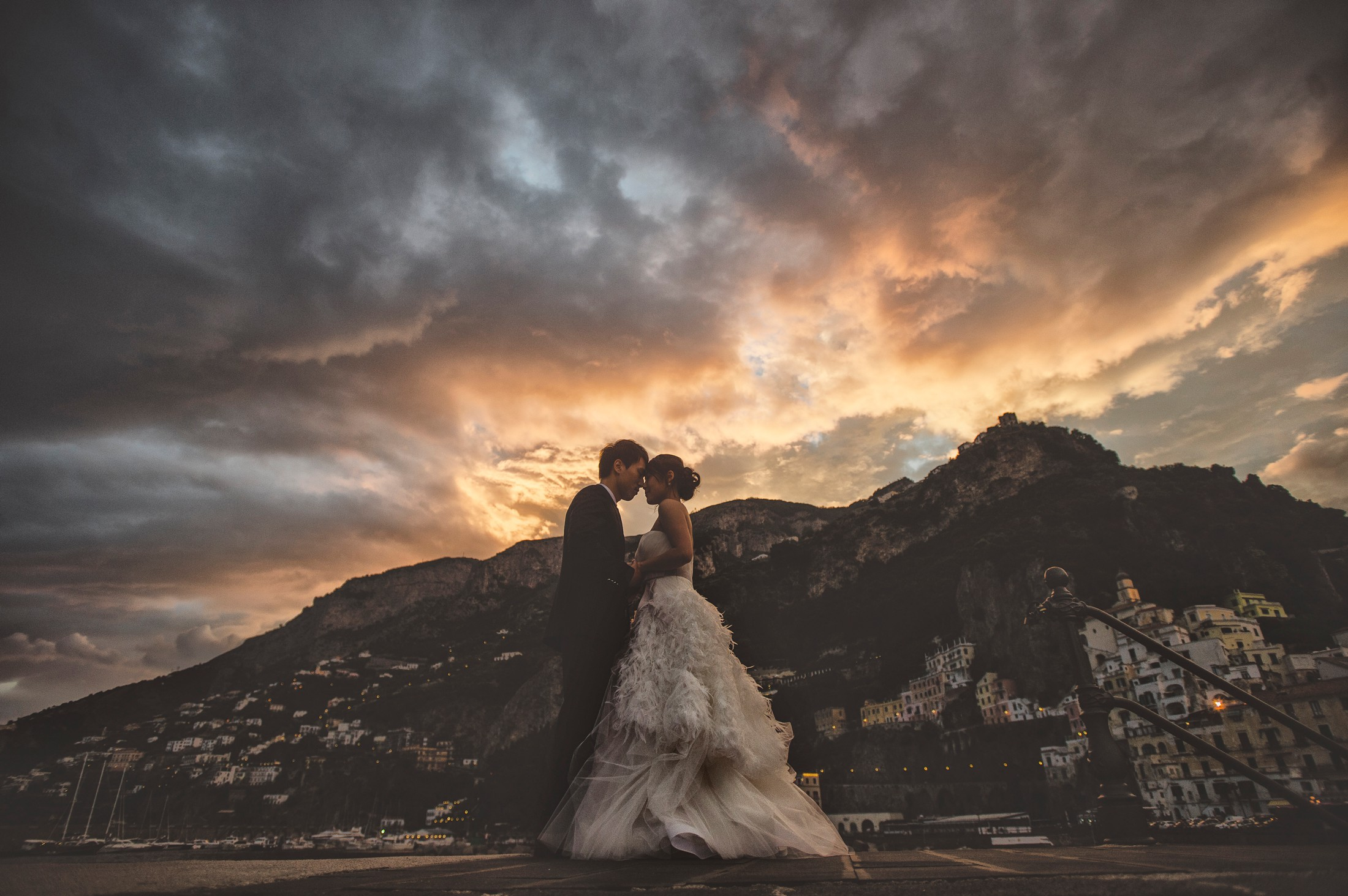 wedding on the amalfi coast bride and groom portrait with amalfi as background at sunset time