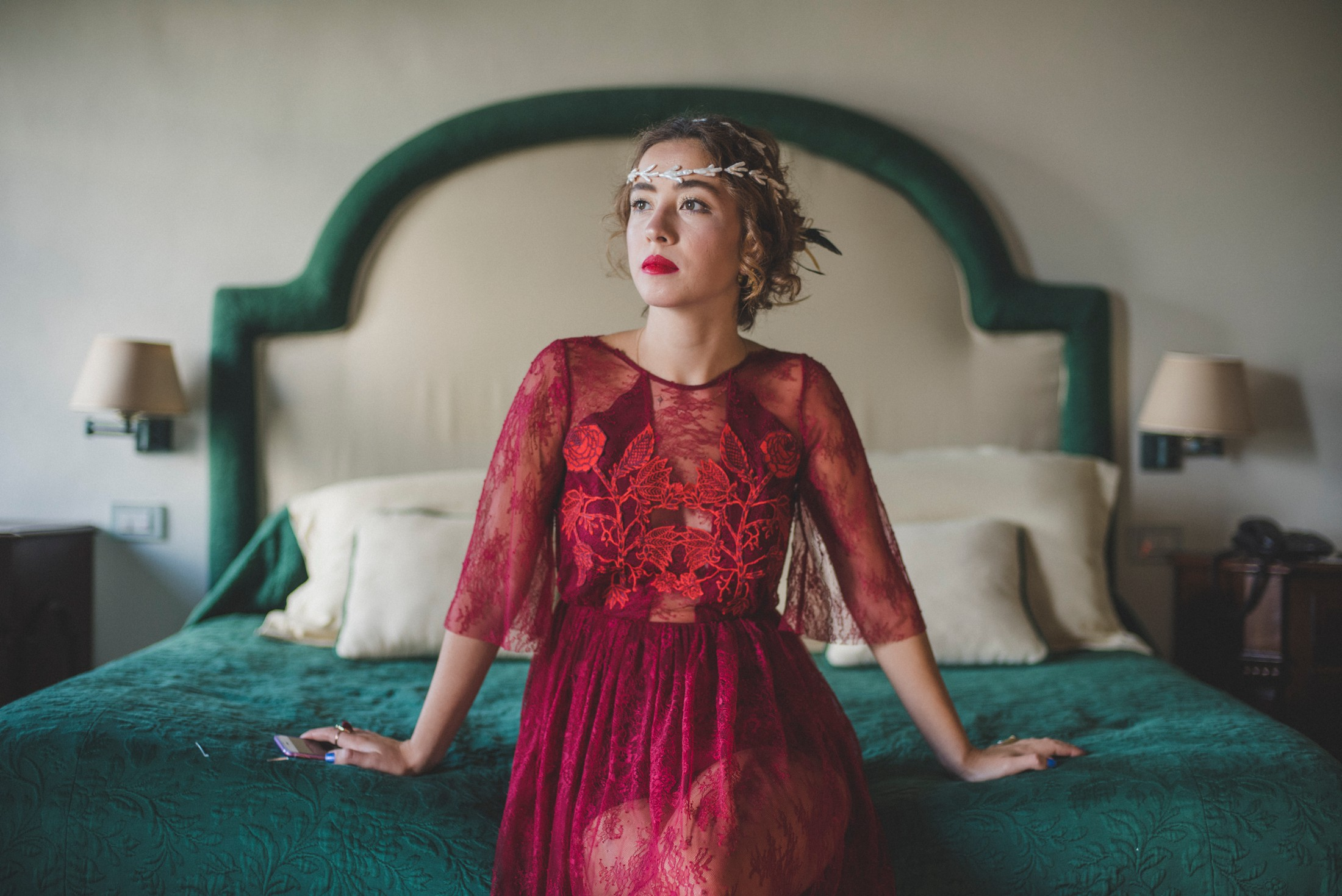 luxury wedding woman in a red dress sitting on the bed