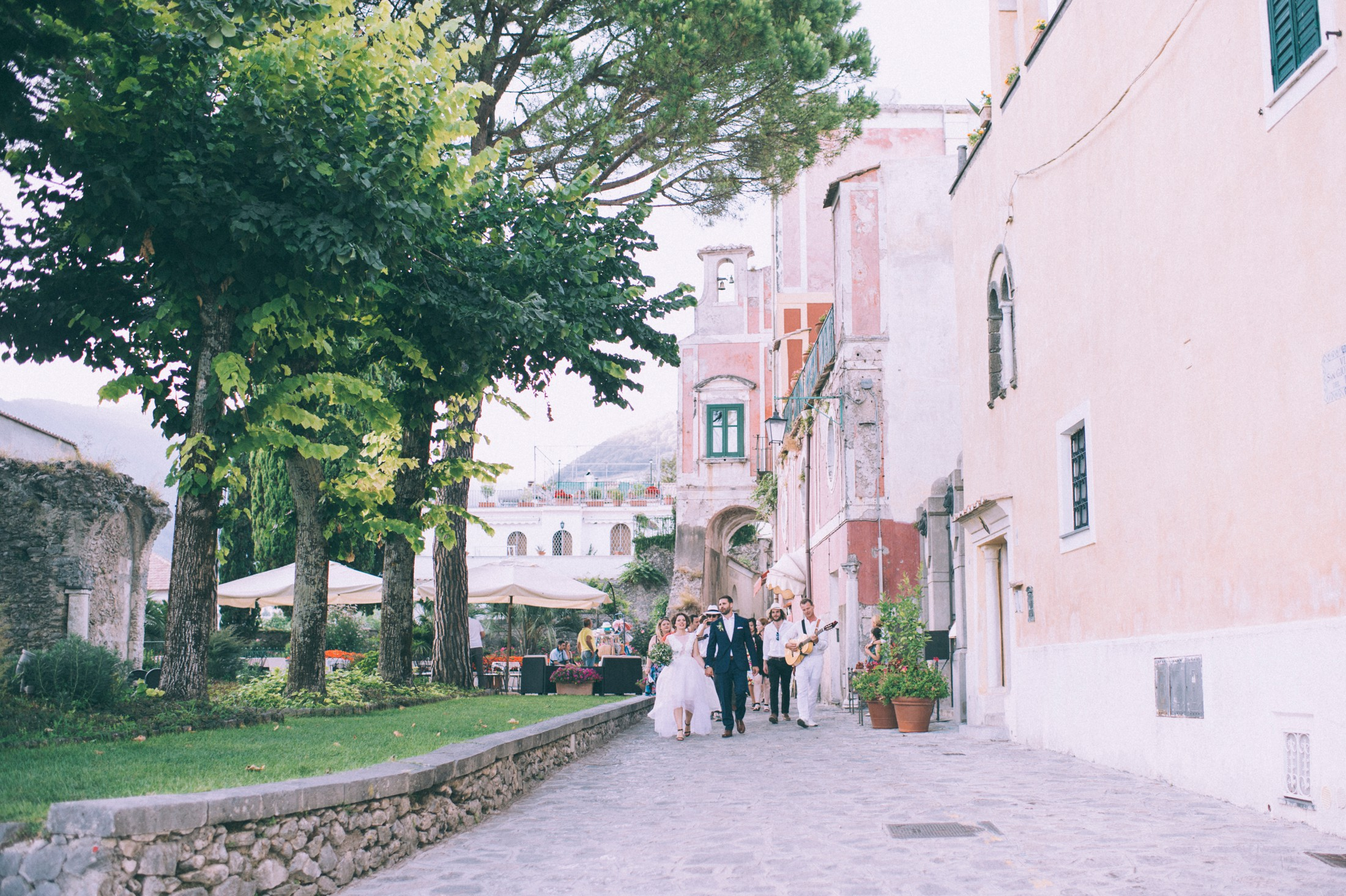 rustic wedding in ravello the bride and the groom walking through ravello with other wedding guests
