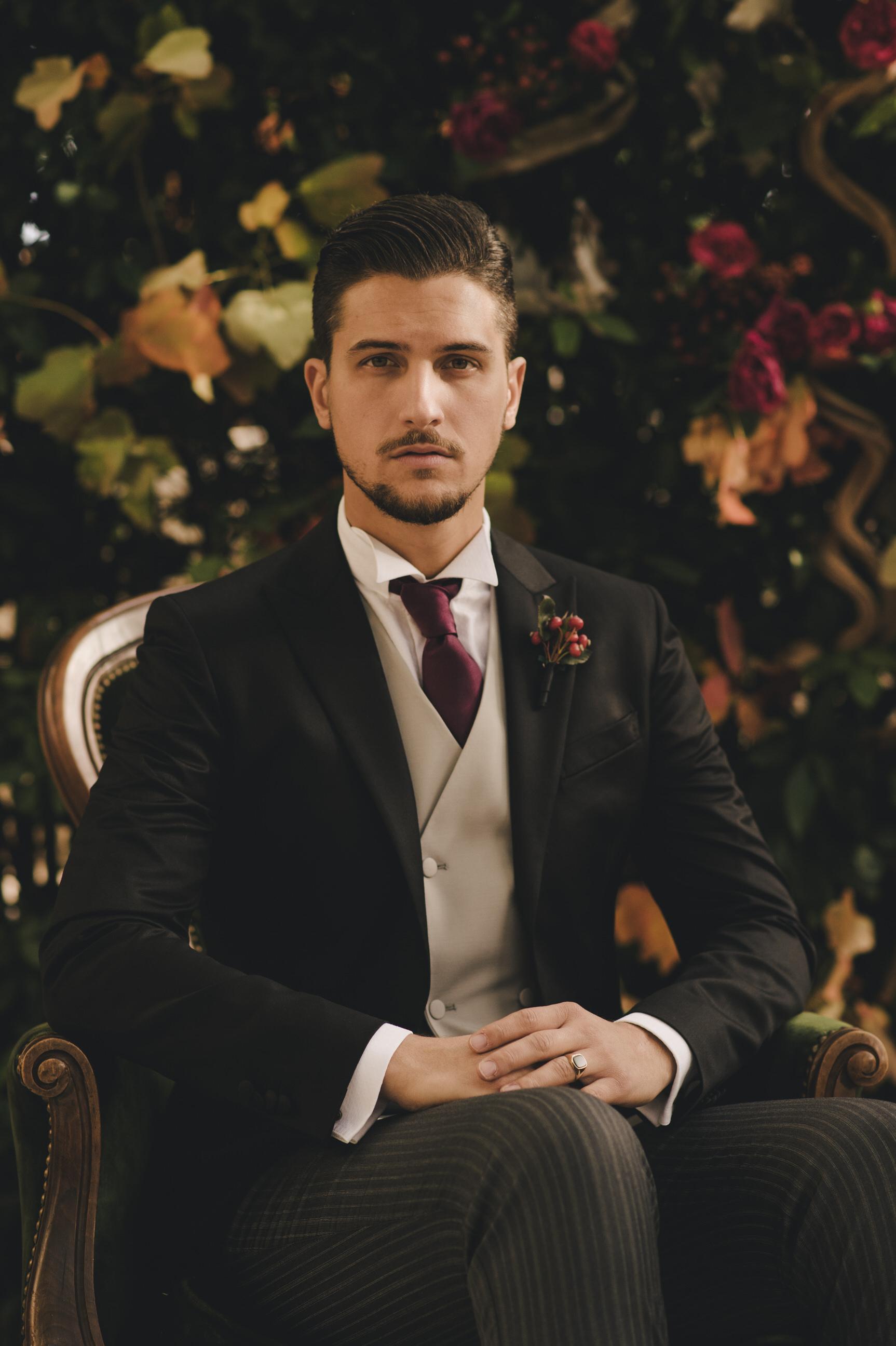 groom's portrait sitting on a green velvet chair