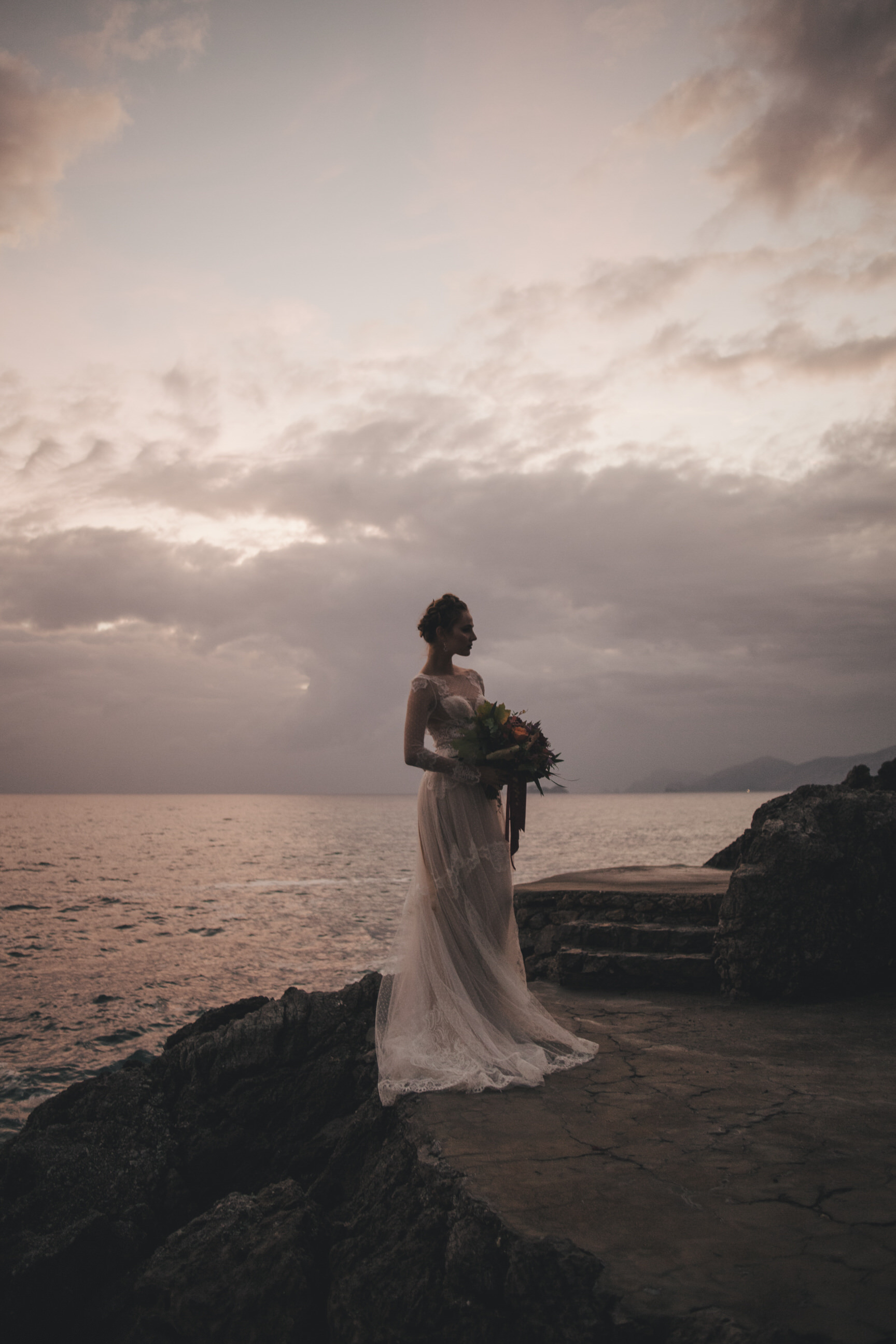 bride's portrait holding the bouquet and standing by the sea