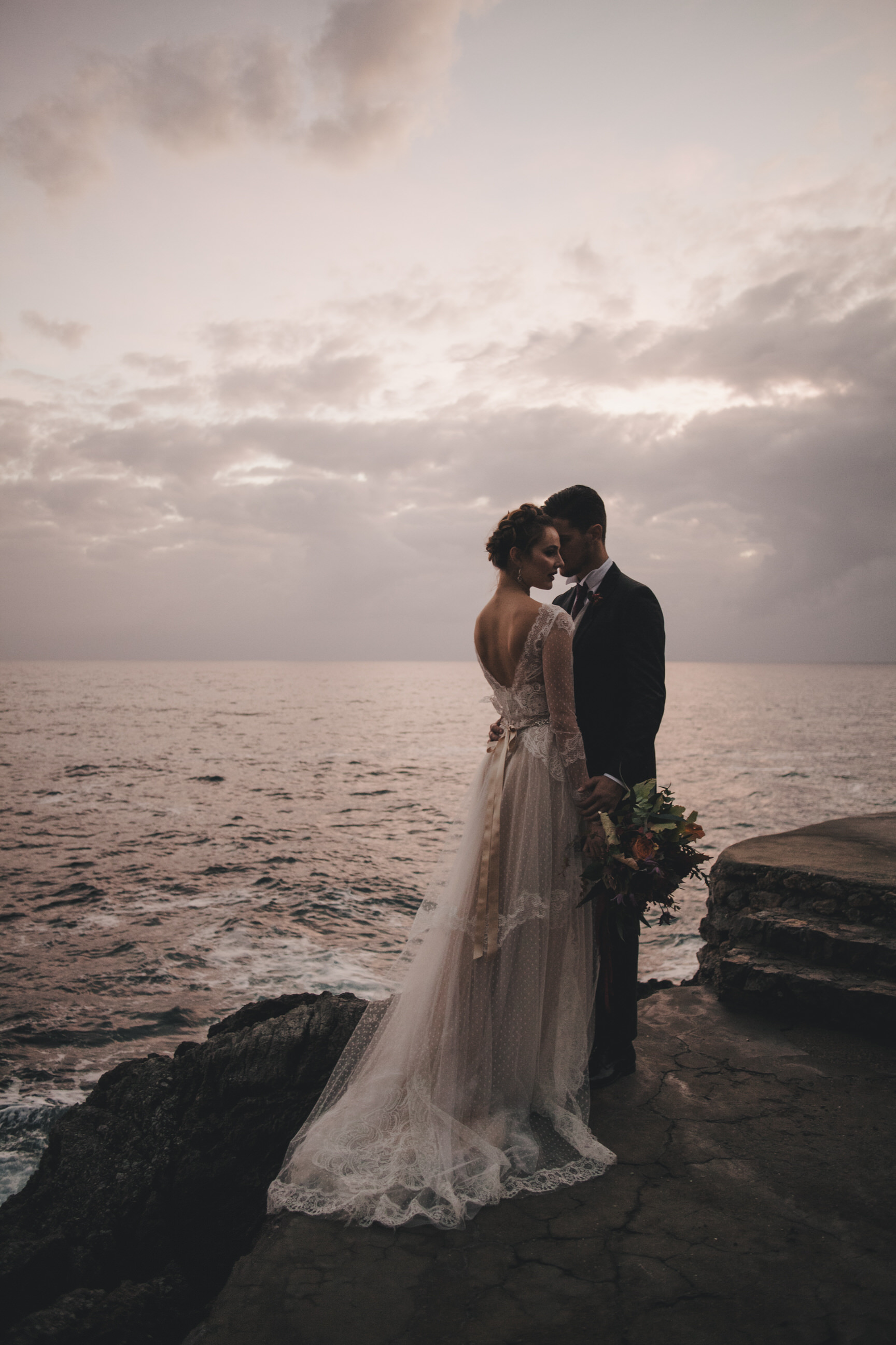 bride and groom's portrait standing by the sea at sunset time