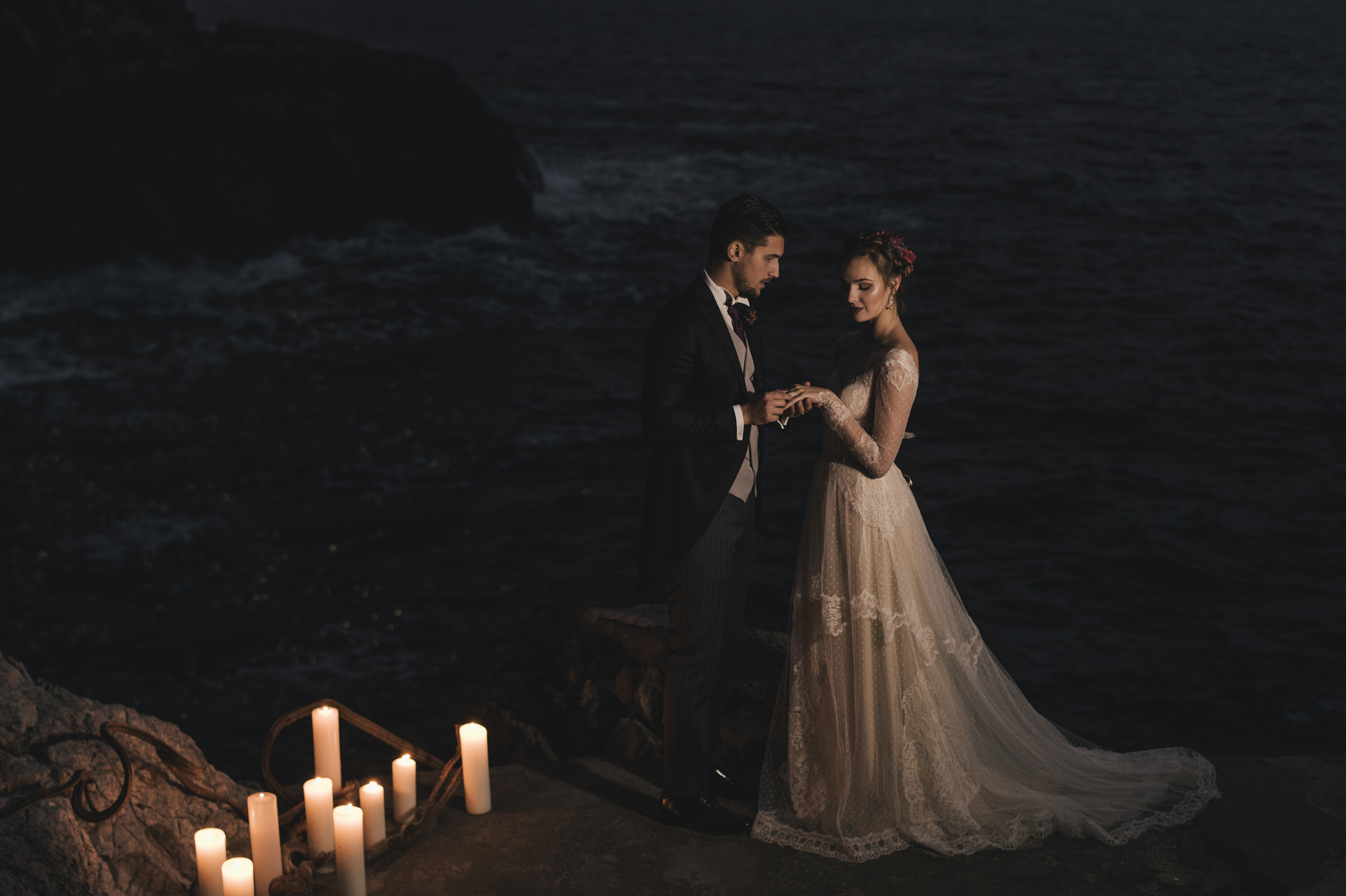 bride and groom exchanging the rings by the sea at night time