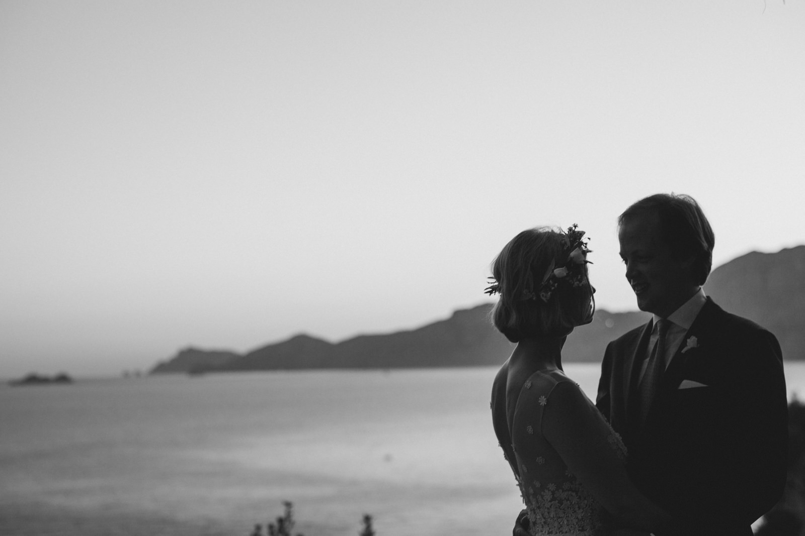 the bride and the groom facing each other in black and white