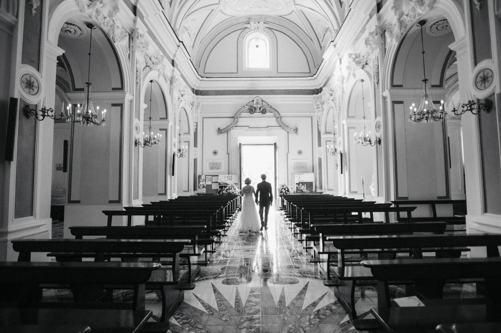 the bride and the groom walk together inside the empty church