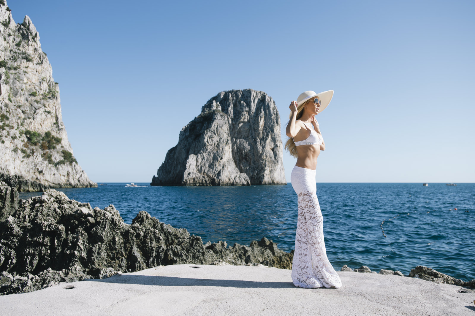 woman with white jumpsuit on the cliffs with the faraglioni as background
