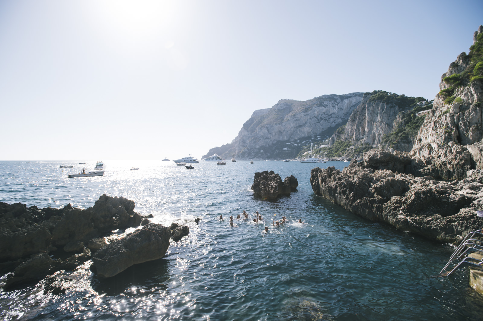 people swimming close to the faraglioni in capri