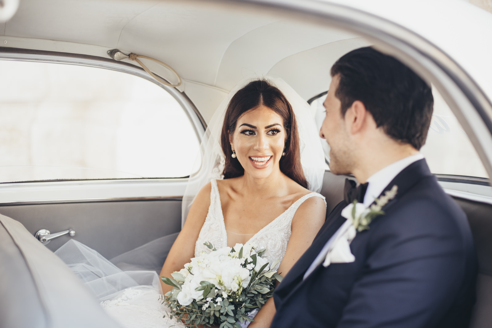 the bride and the groom sitting in their wedding car