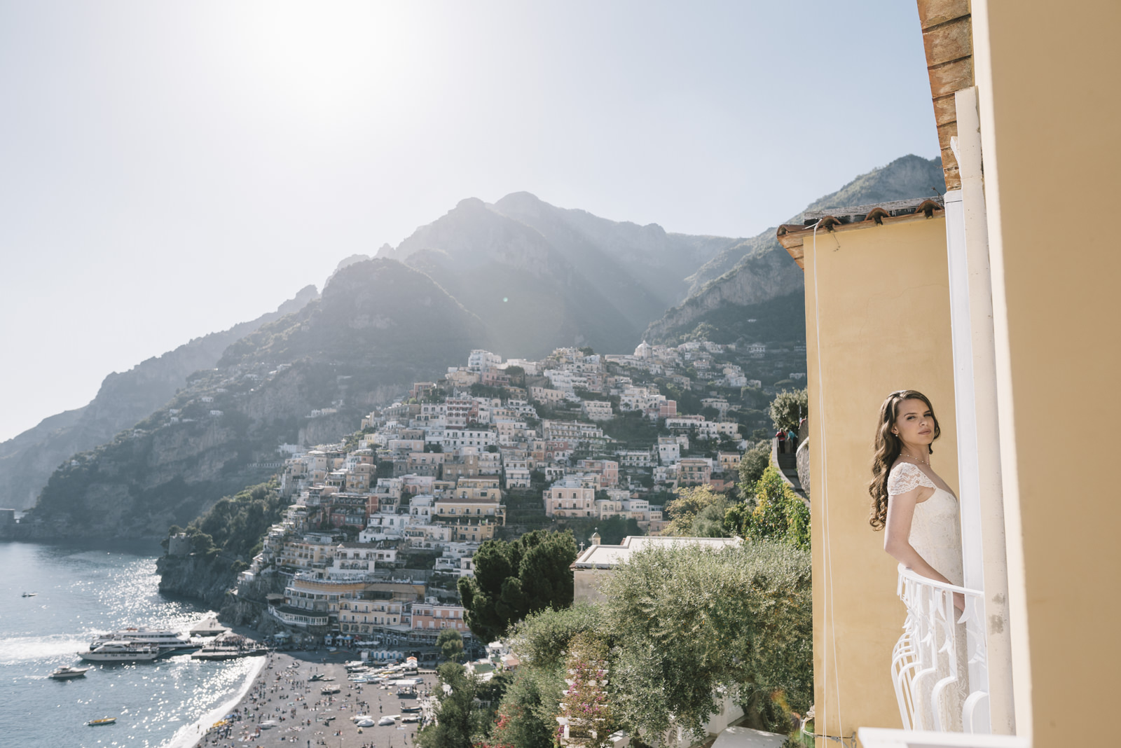 the bride on a balcony with positano on the background