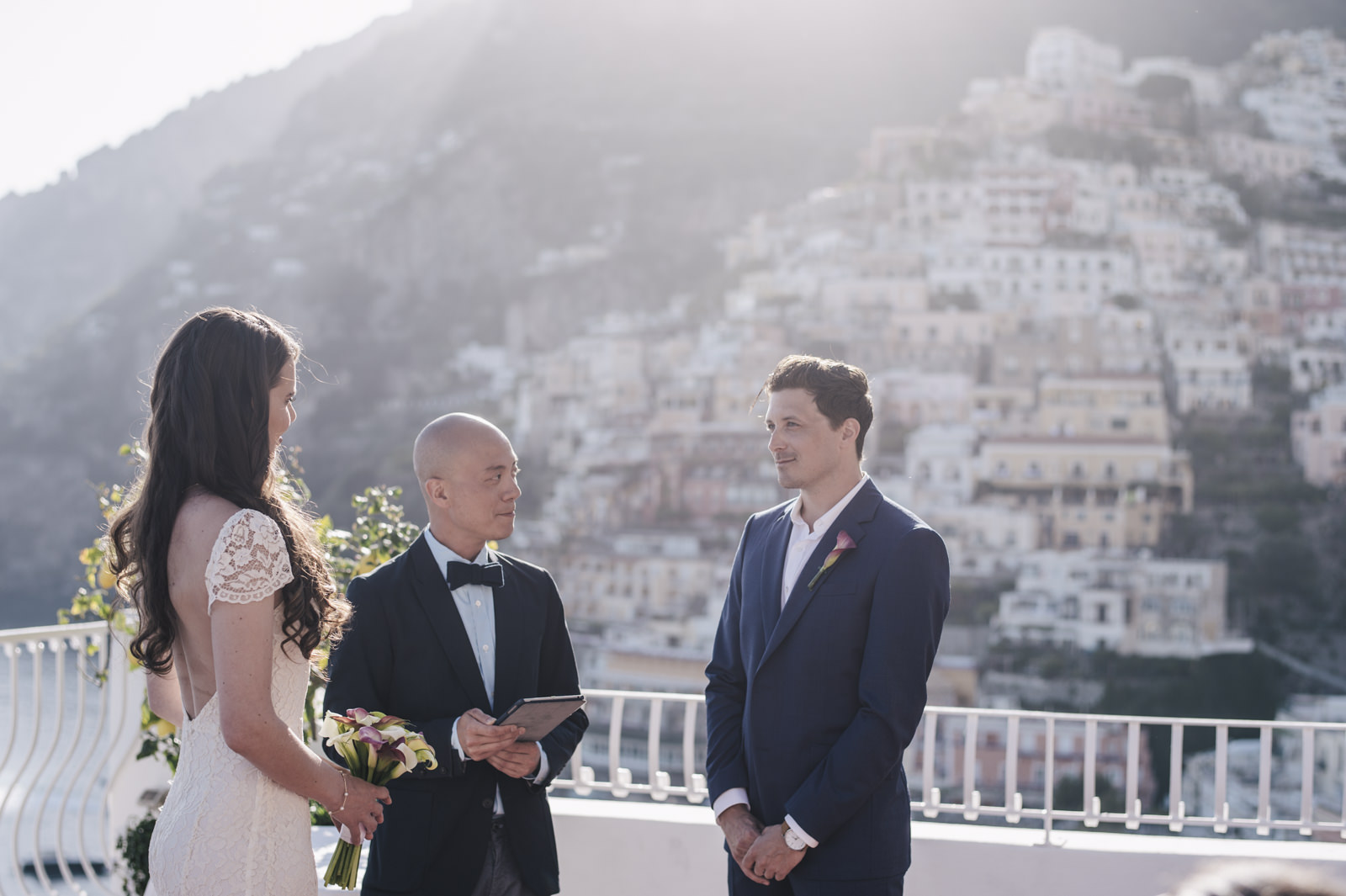 the bride, the groom and the celebrant during the wedding ceremony with positano as background