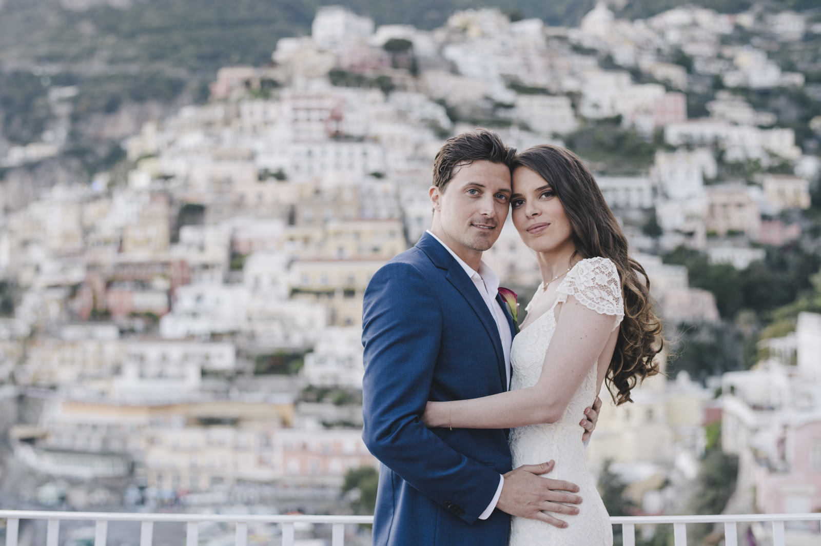 bride and groom's portrait with positano as background