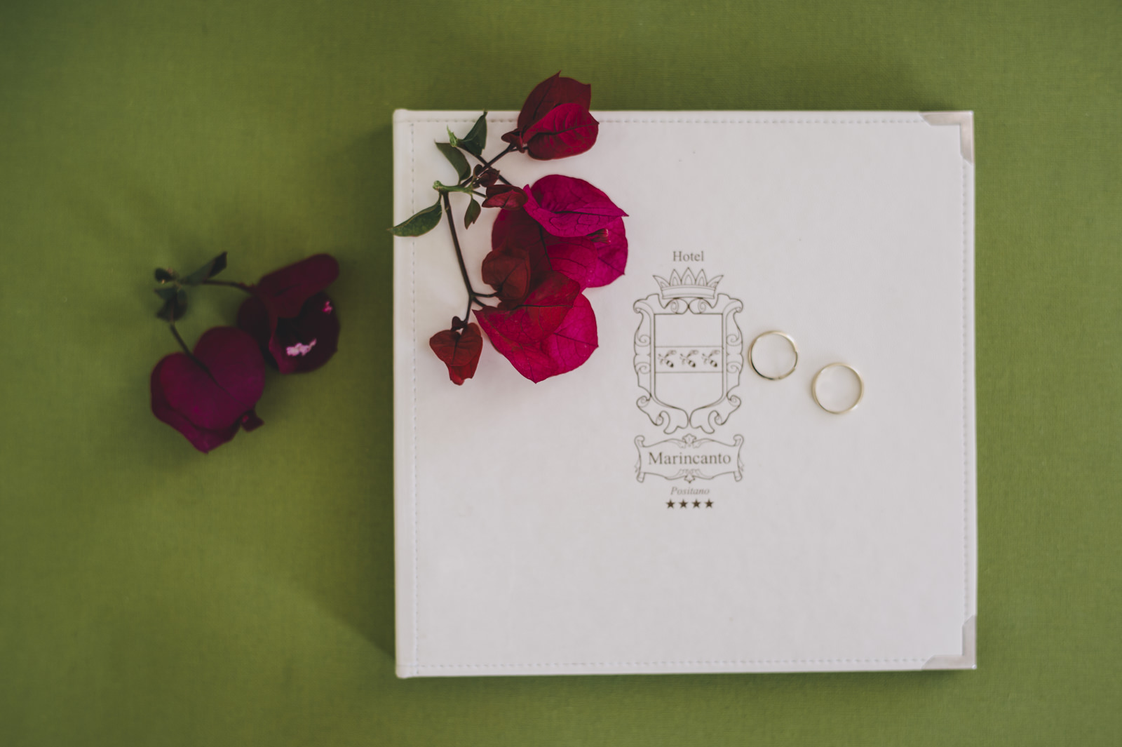wedding rings on the invitation card with red flowers