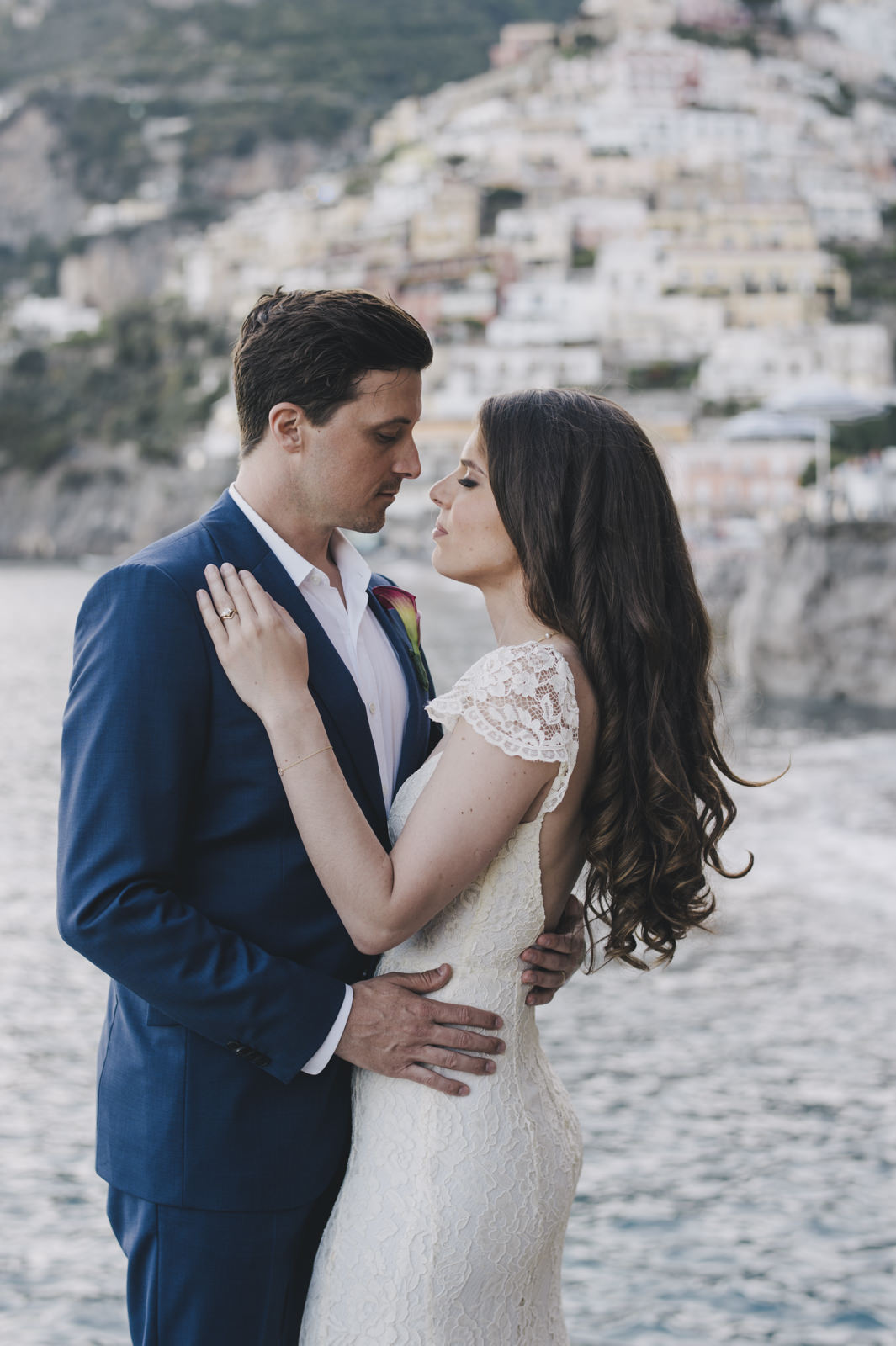 the bride and the groom facing each other on the beach of positano