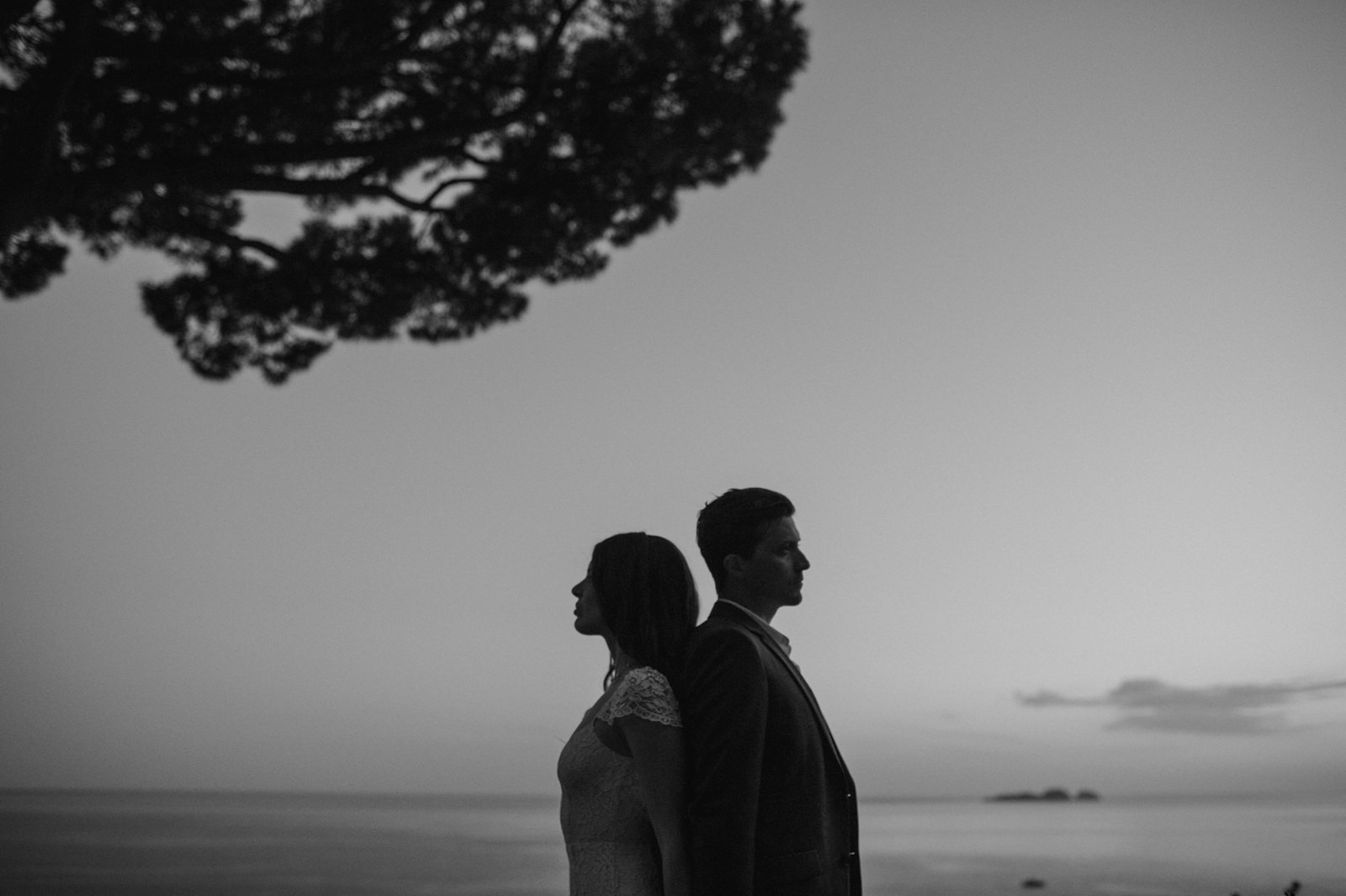 bride and groom standing shoulder against shoulder in black and white