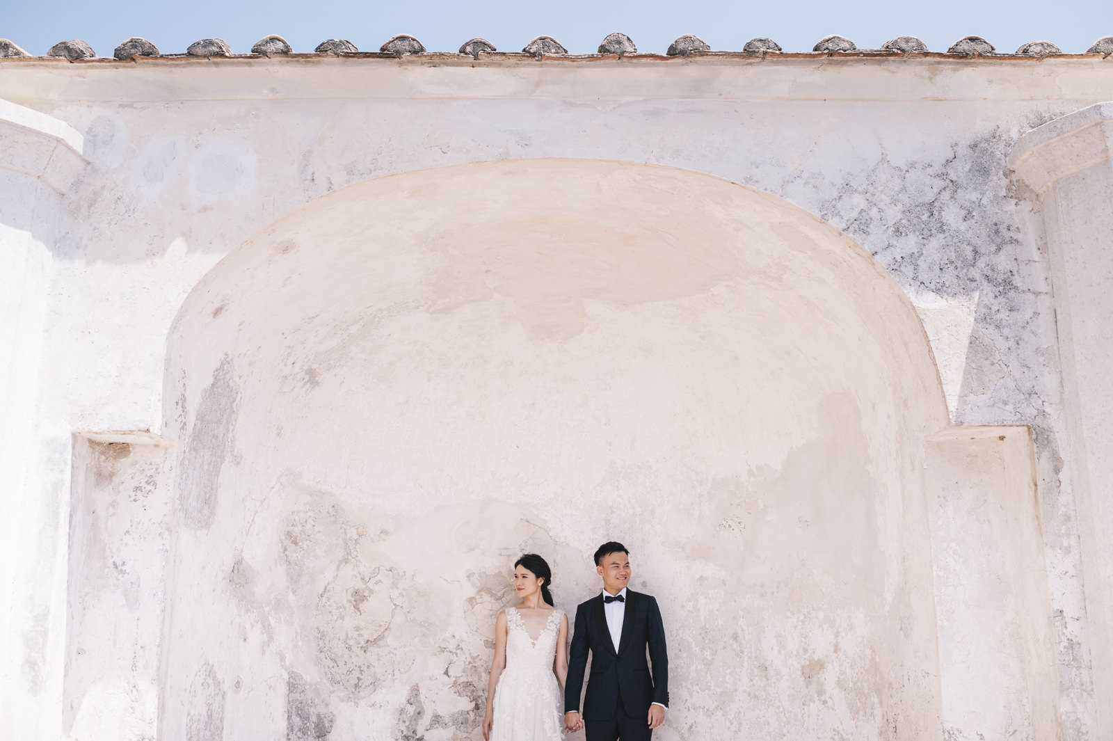 the bride and the groom standing side by side and lining against a white wall