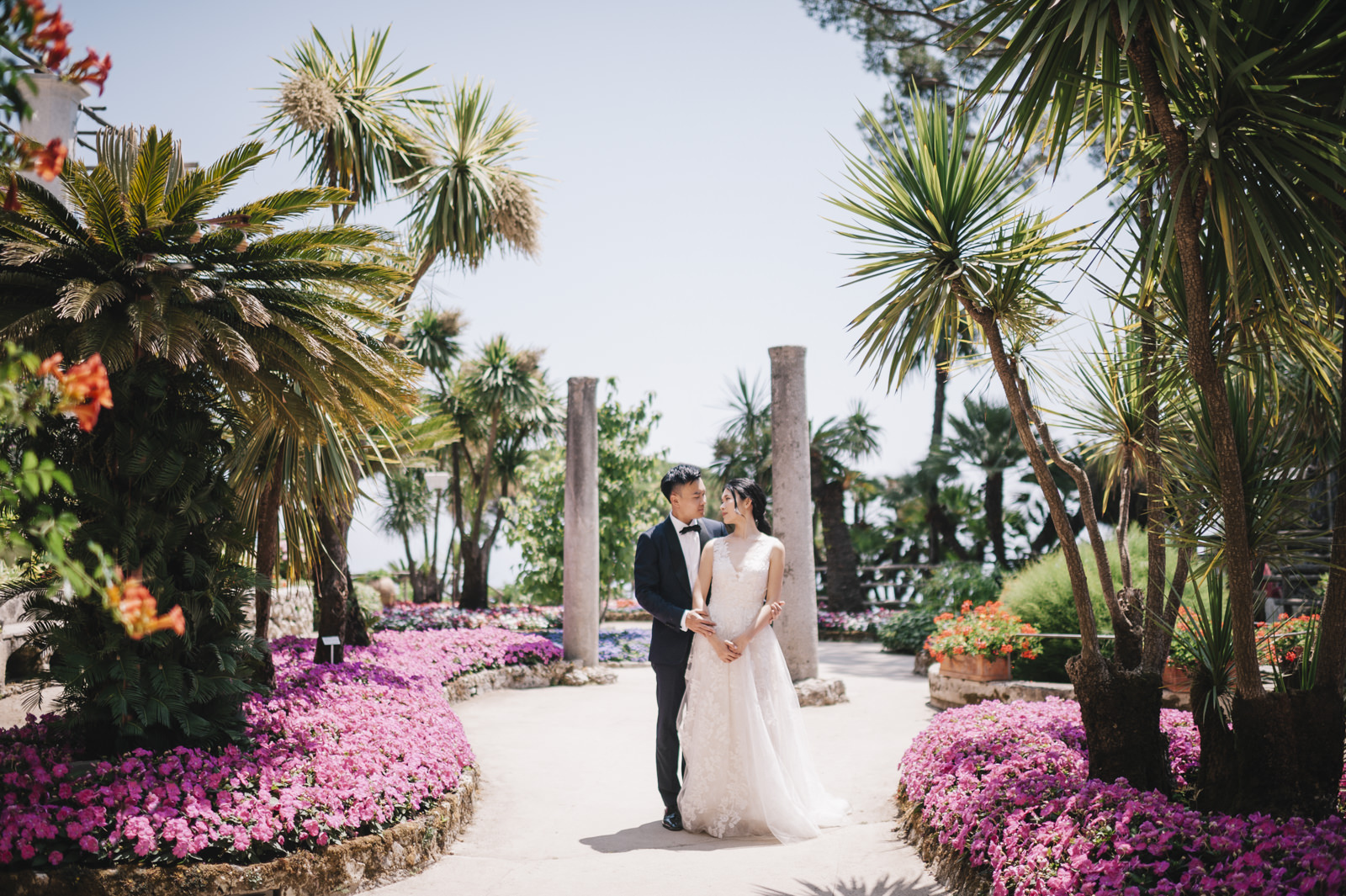 bride and groom's portrait at villa rufolo surrounded by multicolored flowers