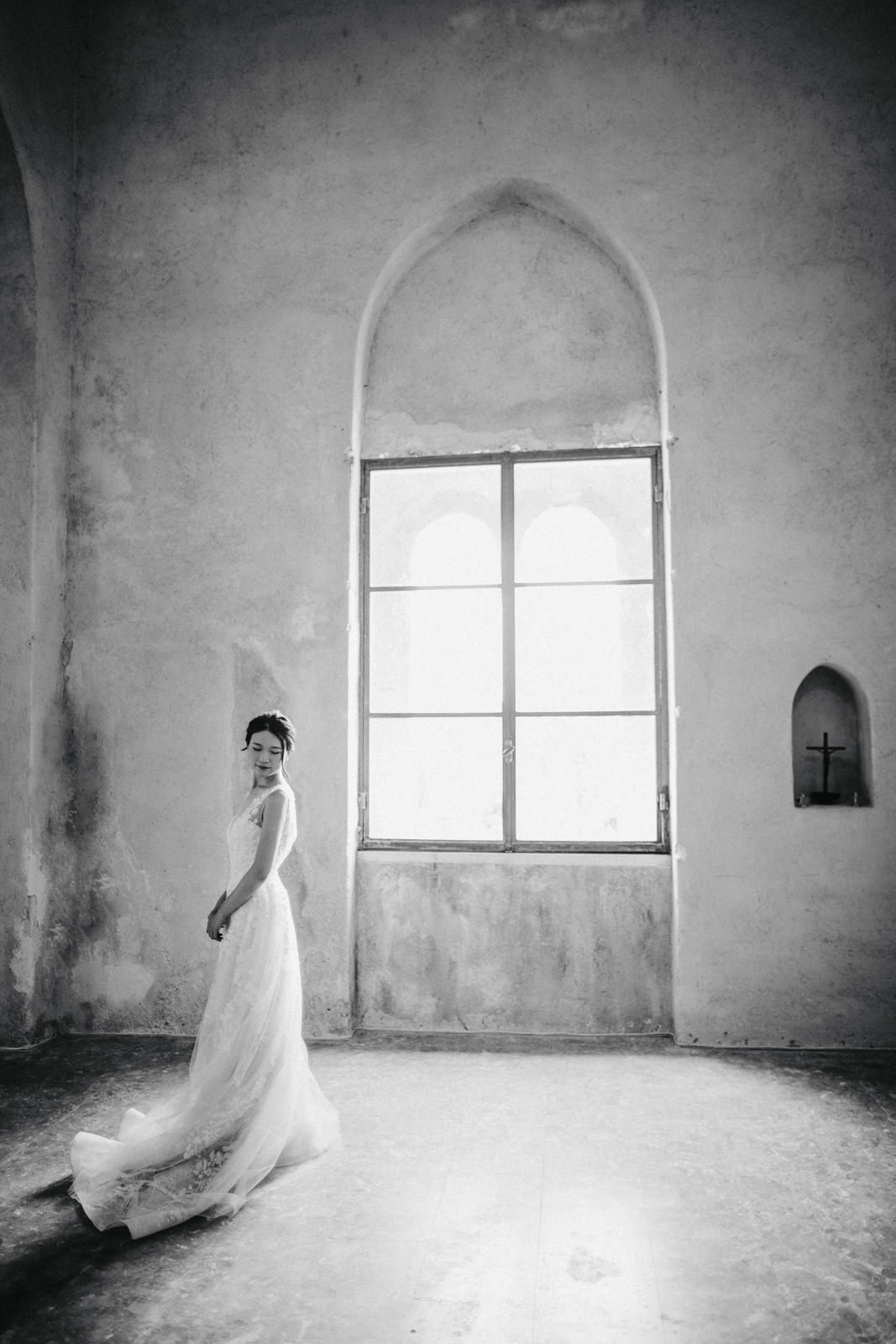 bride standing by a big window inside the church in black and white