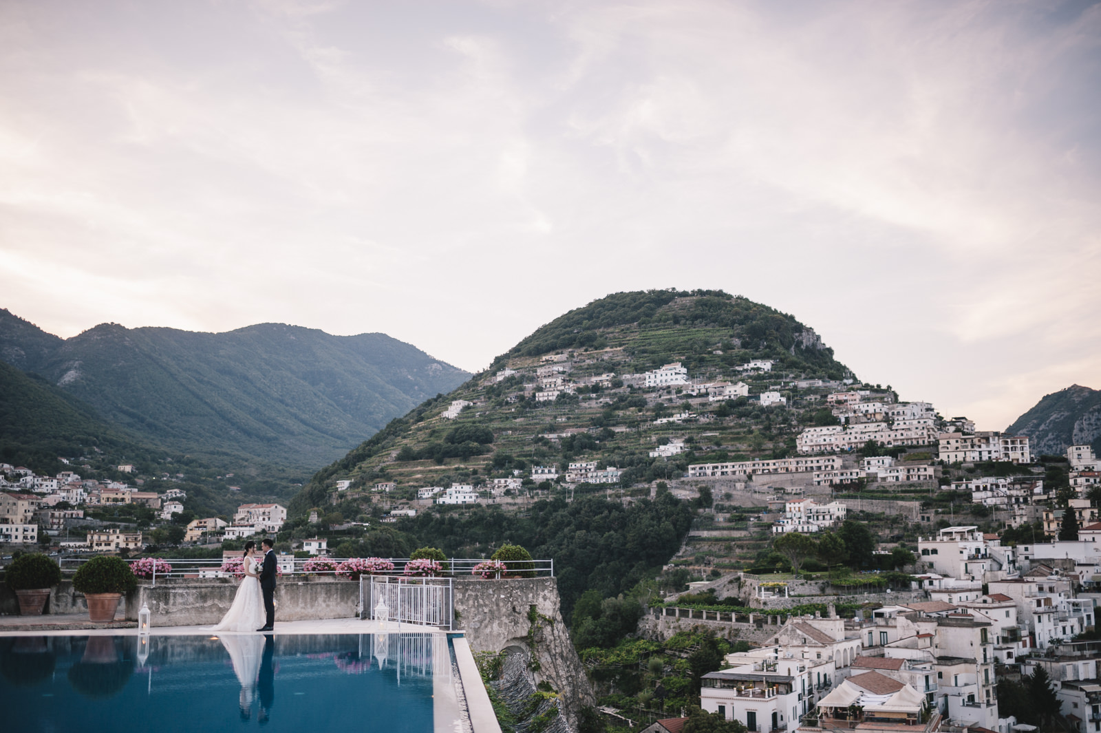 bride and groom by the infinity pool of the belmont hotel caruso and ravello on the background