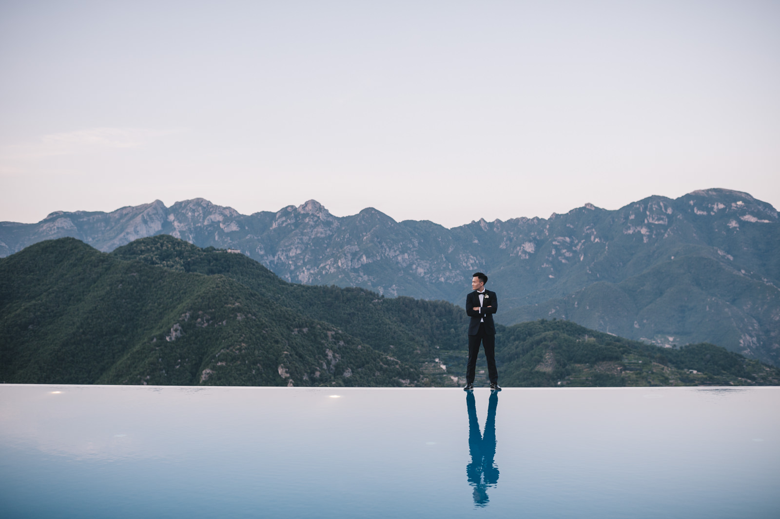 the groom standing by the infinity pool of belmont hotel caruso
