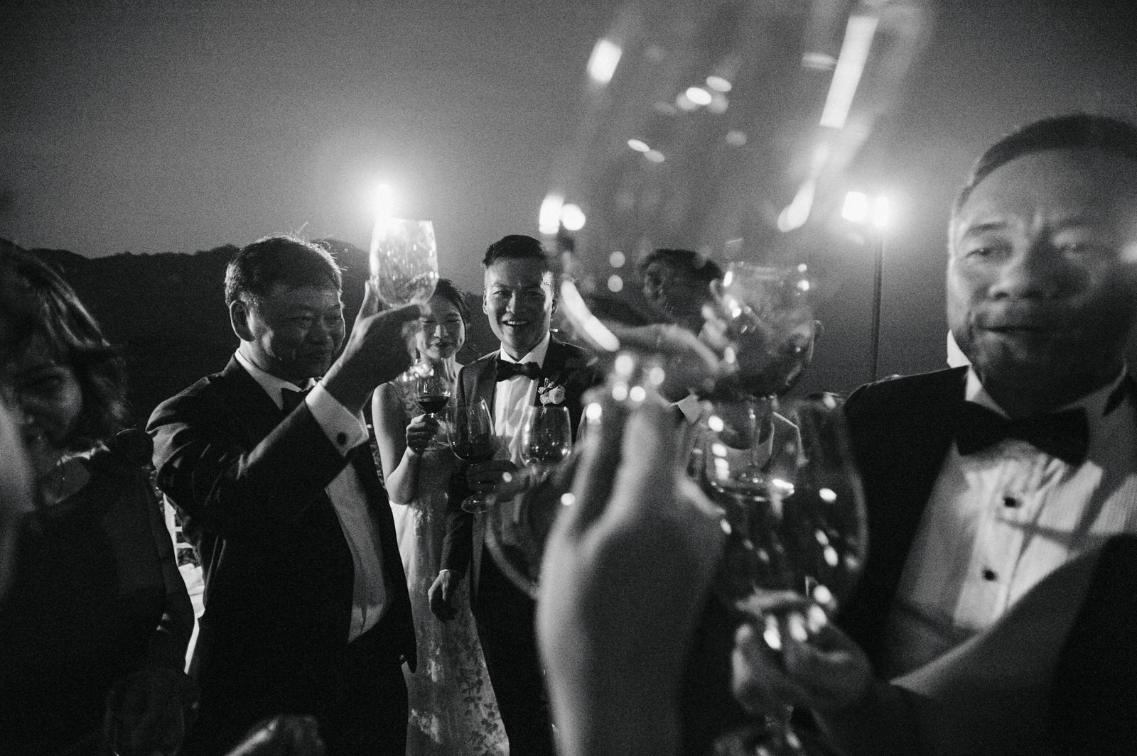 the groom having a toast with some friends in black and white