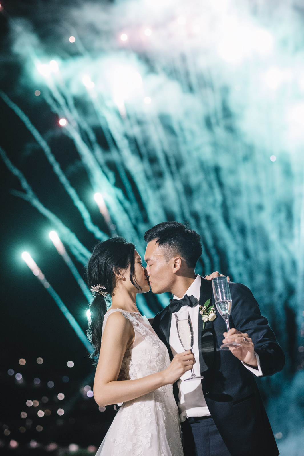 the groom kissing the bride during the fireworks