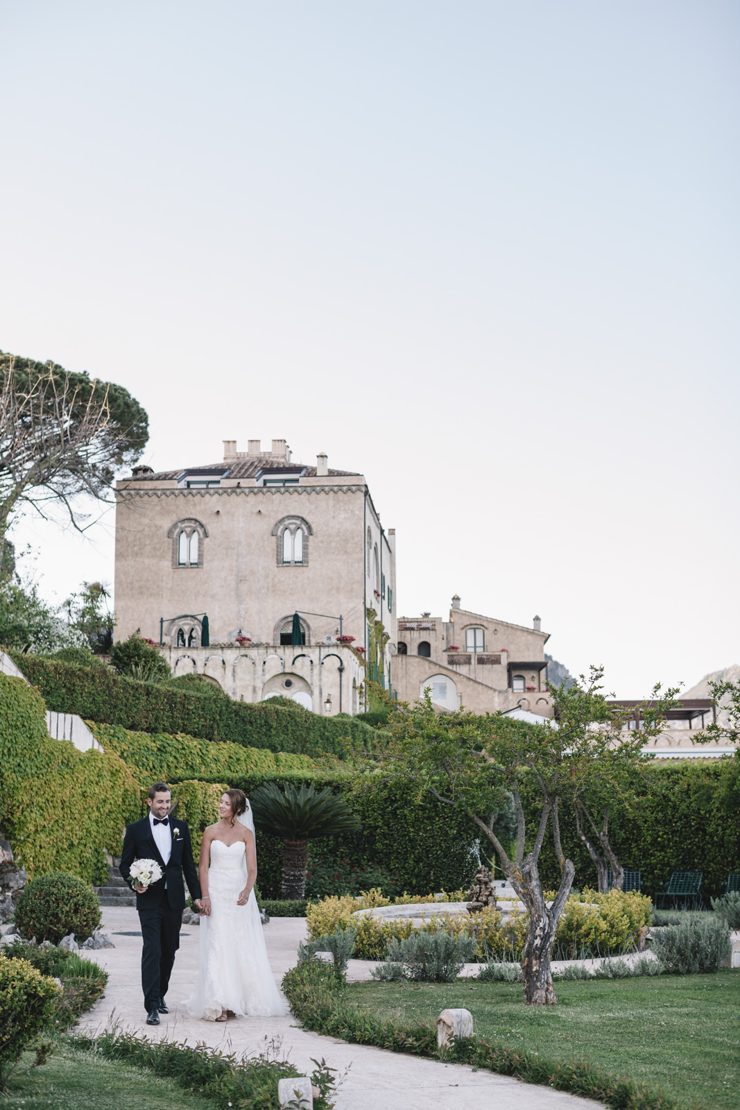 the bride and the groom walking together in villa cimbrone