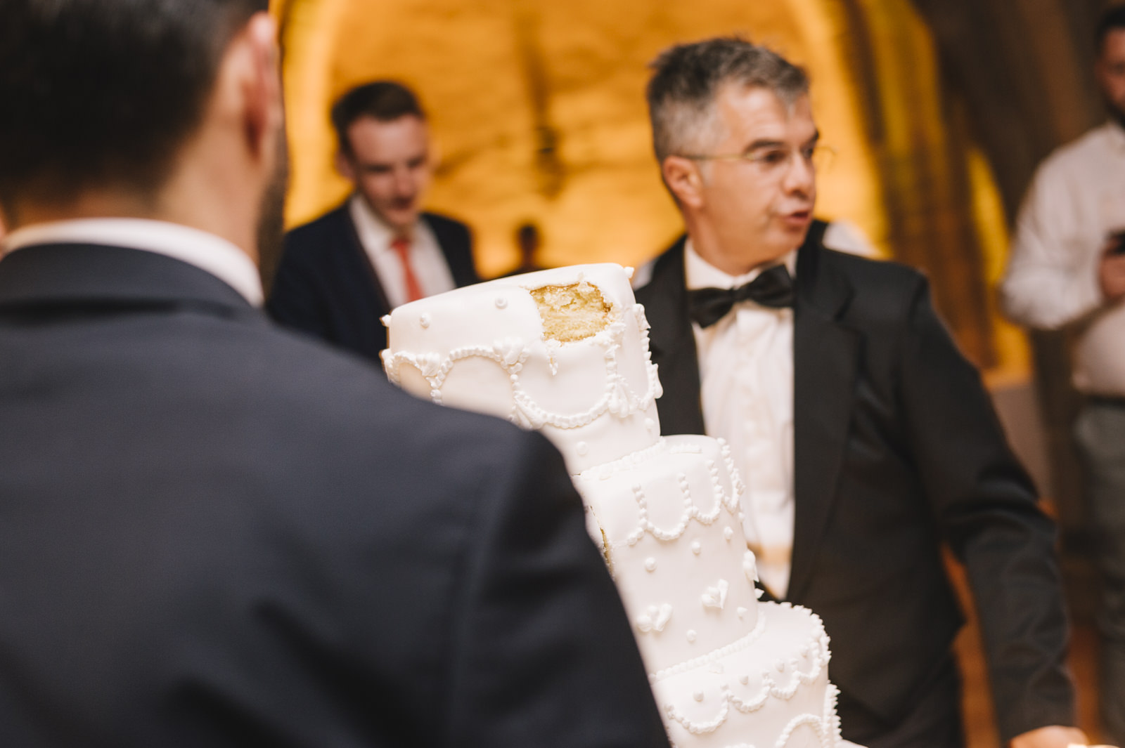 the maitre and his assistant caring the wedding cake