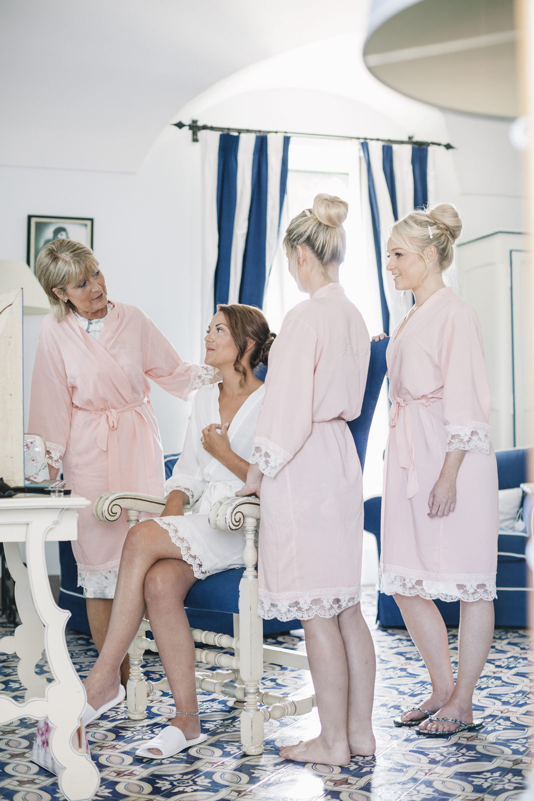 the bride surrounded by the bridesmaids during the preparation
