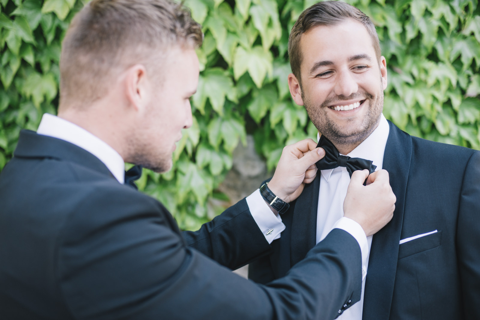 the best man adjusting the groom's bow tie