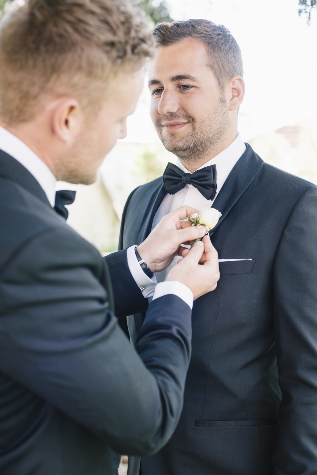 the best man put the boutonniere on the groom's jacket