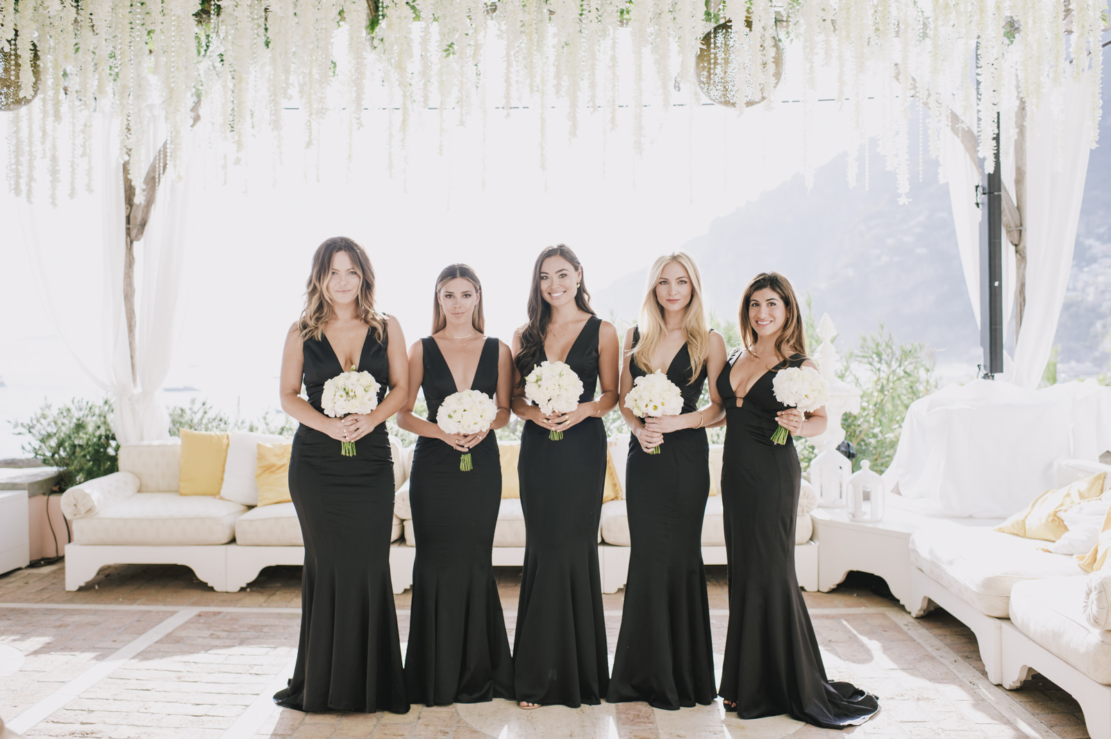 bridesmaids with black dress and bouquets