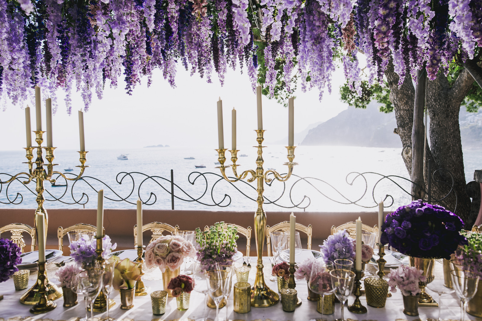 wedding table with candles violet flowers and wisteria