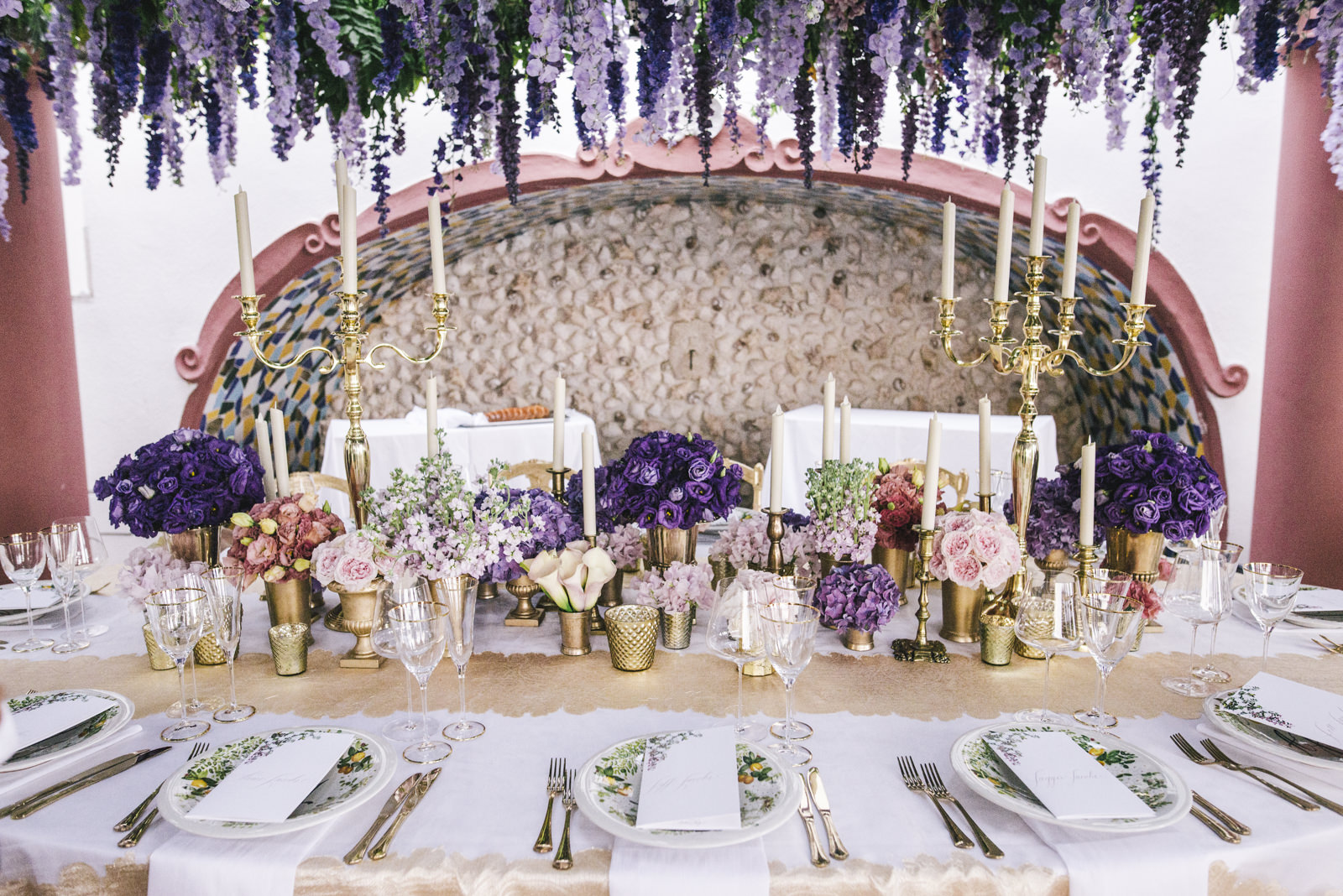 wedding table with violet flower, candles and wisteria
