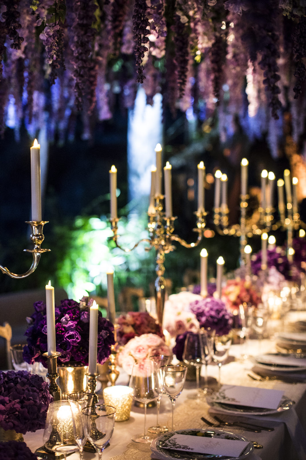 wedding table with violet and red flowers, candle lighted on and wisteria