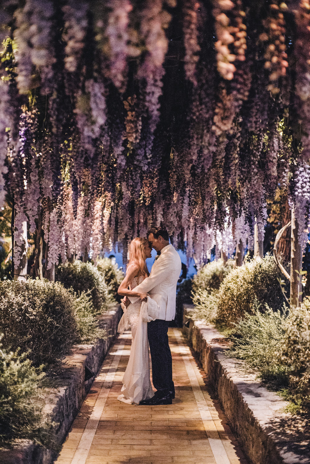 the bride and the groom facing each other under the wisteria by night
